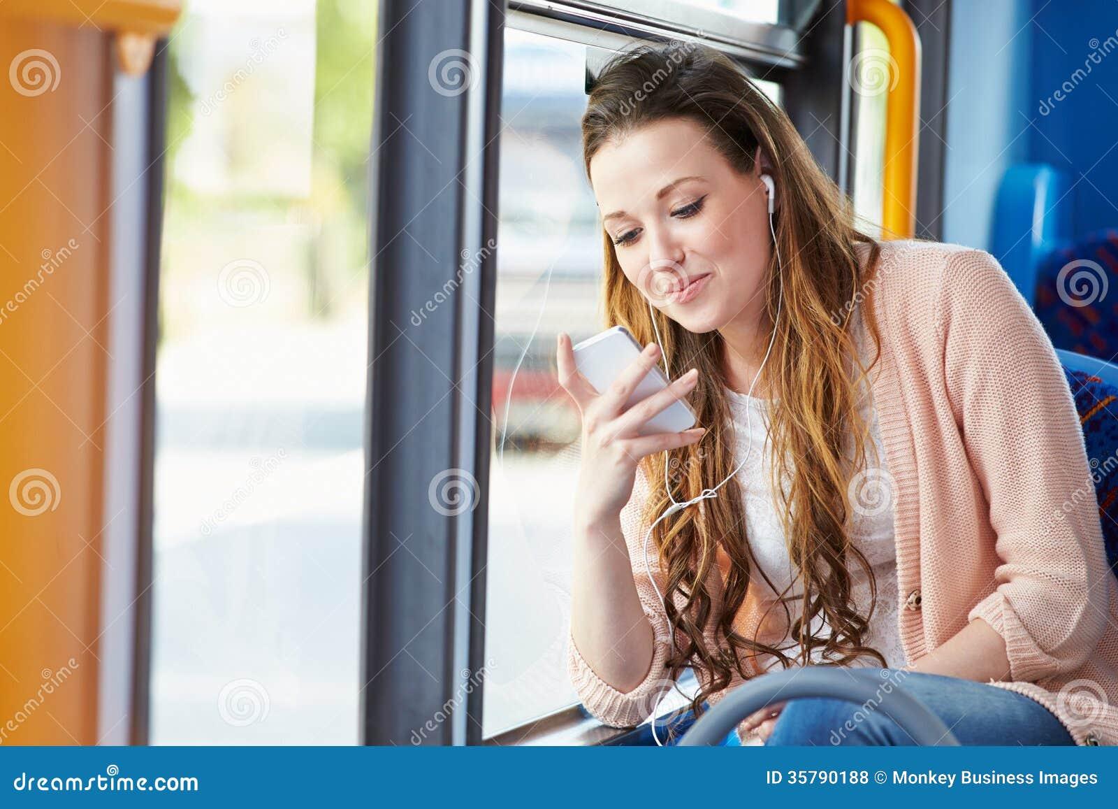 Νέα γυναίκα που φορά τα ακουστικά που ακούνε τη μουσική στο λεωφορείο