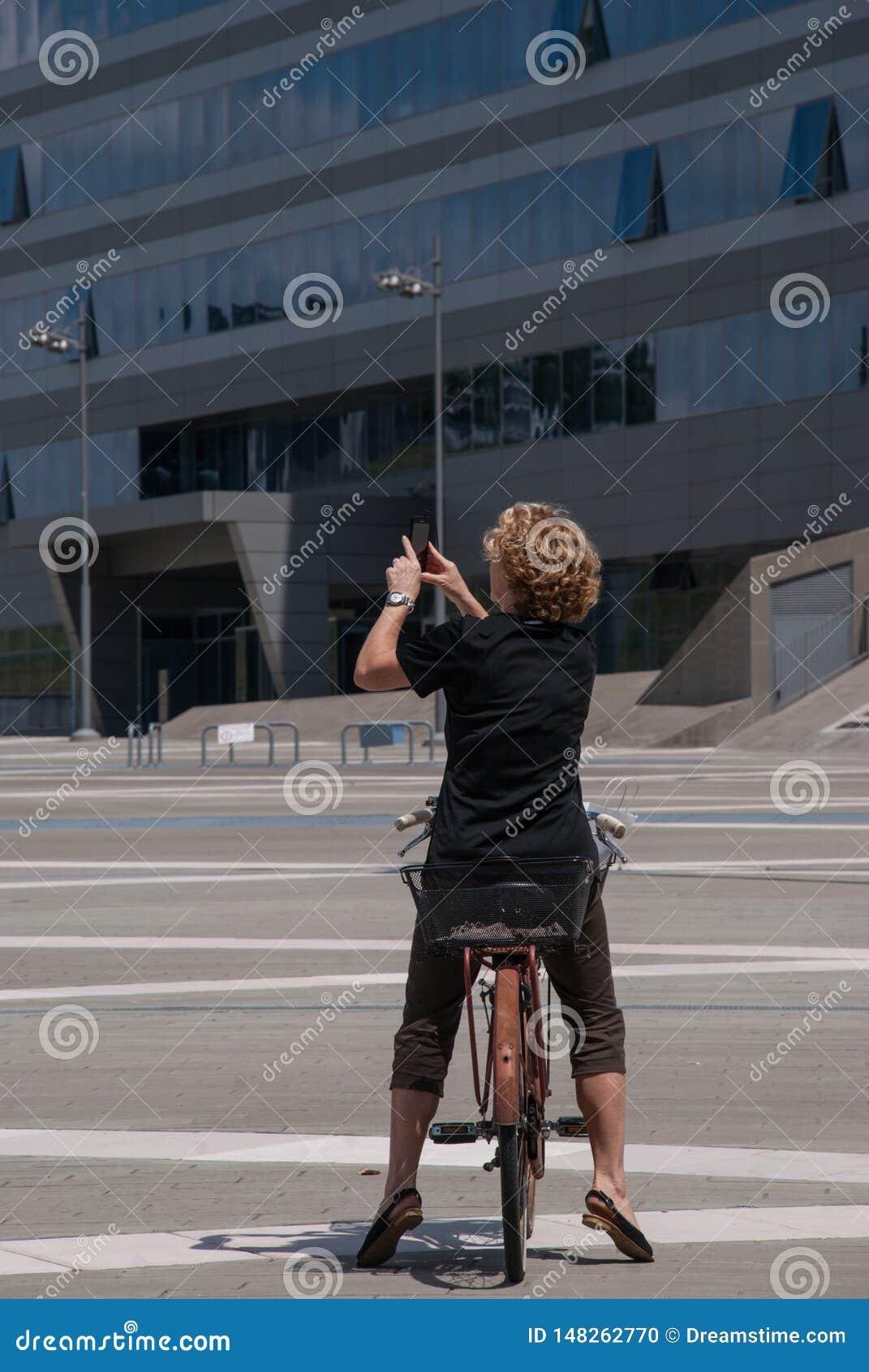 Νέα γυναίκα που φωτογραφίζει με ένα κινητό τηλέφωνο