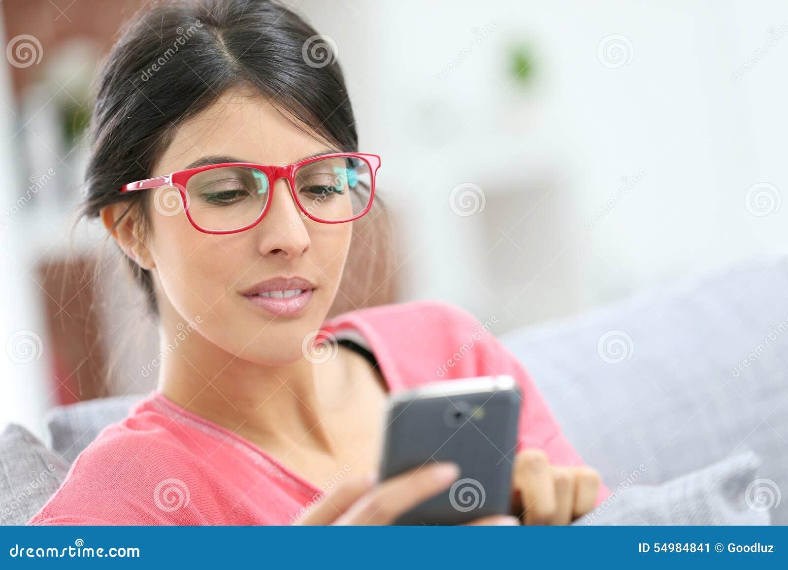 Νέα γυναίκα που χρησιμοποιεί στο σπίτι το smartphone