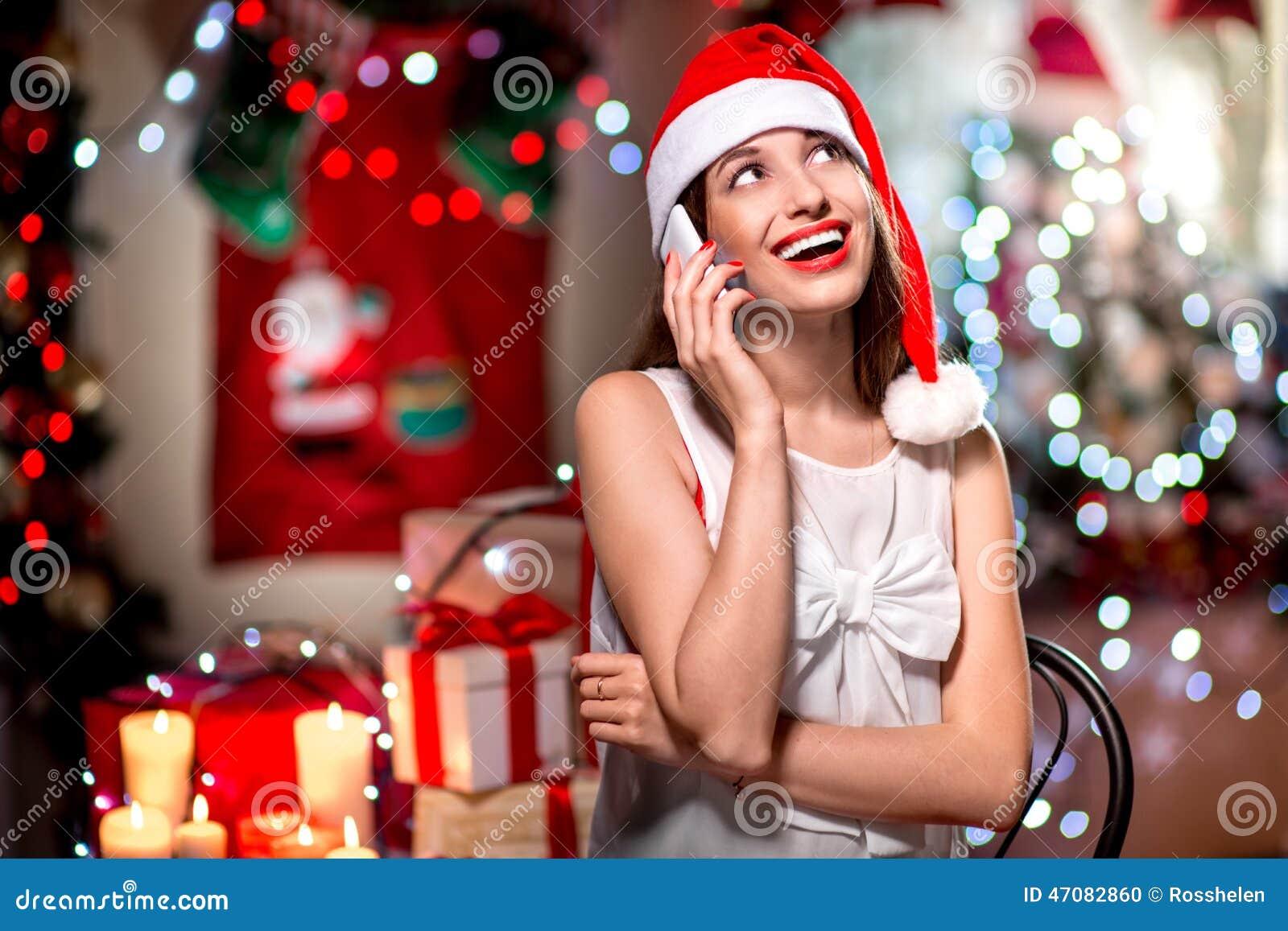 Νέα γυναίκα που χρησιμοποιεί το κινητό τηλέφωνο στα Χριστούγεννα