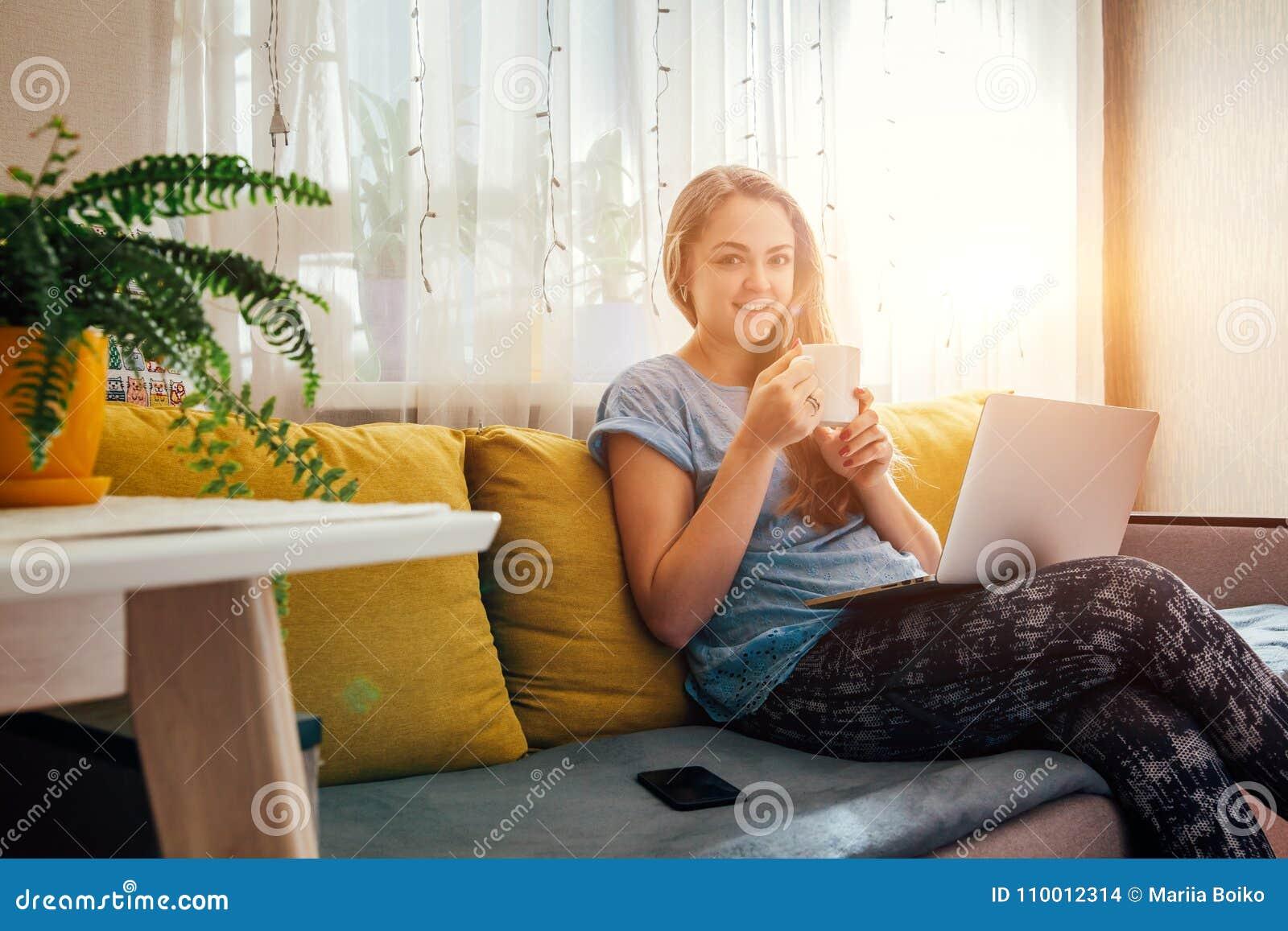 Νέα γυναίκα που χρησιμοποιεί το lap-top της στο καθιστικό