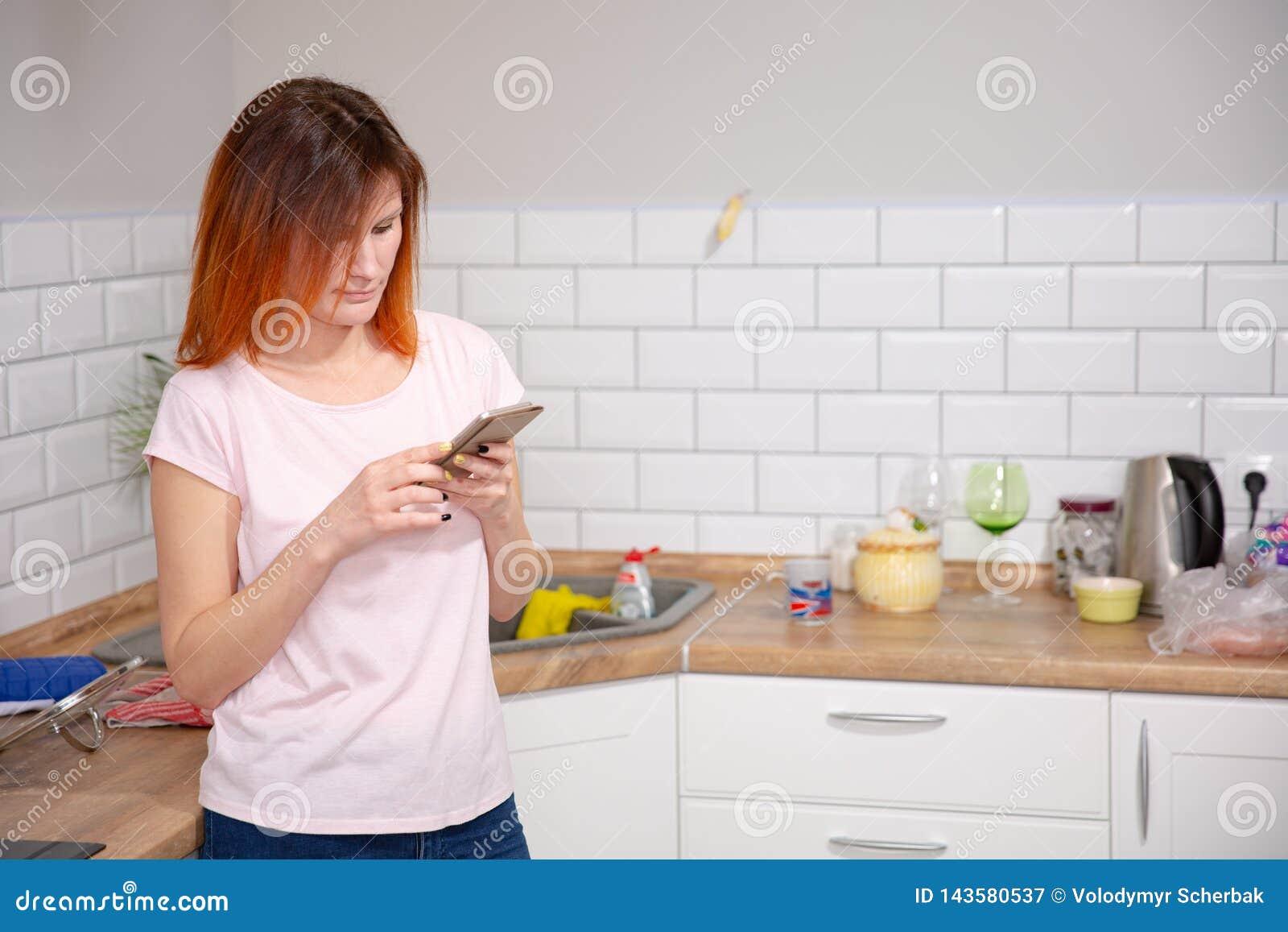 Νέα γυναίκα που χρησιμοποιεί το smartphone που κλίνει στην κουζίνα σε ένα σύγχρονο σπίτι τηλεφωνικό μήνυμα ανάγνωσης γυναικών red