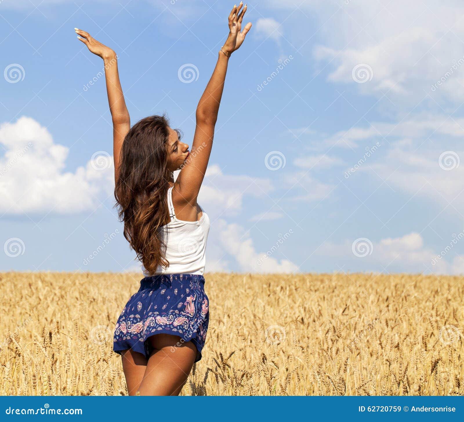 Download Νέα γυναίκα σε έναν χρυσό τομέα σίτου Στοκ Εικόνα - εικόνα από κορίτσι, σύννεφα: 62720759