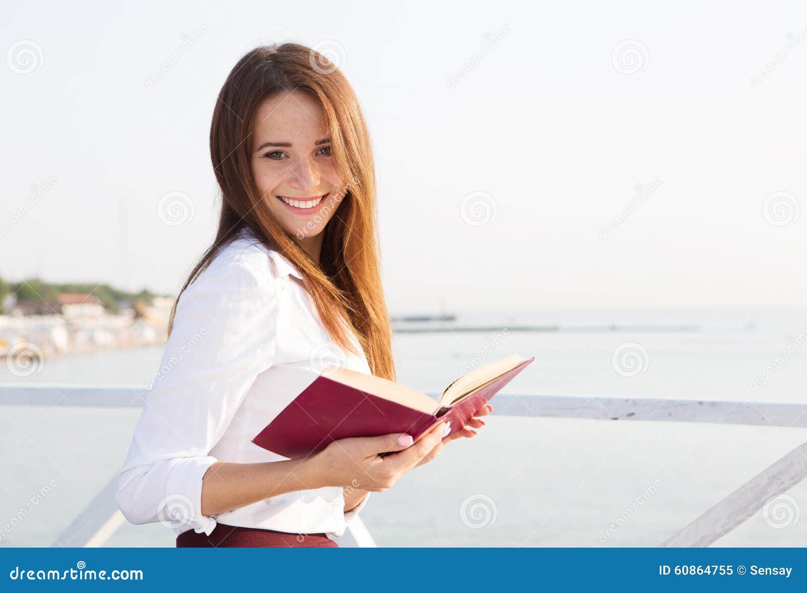 Νέα γυναίκα σπουδαστής με το βιβλίο στην παραλία