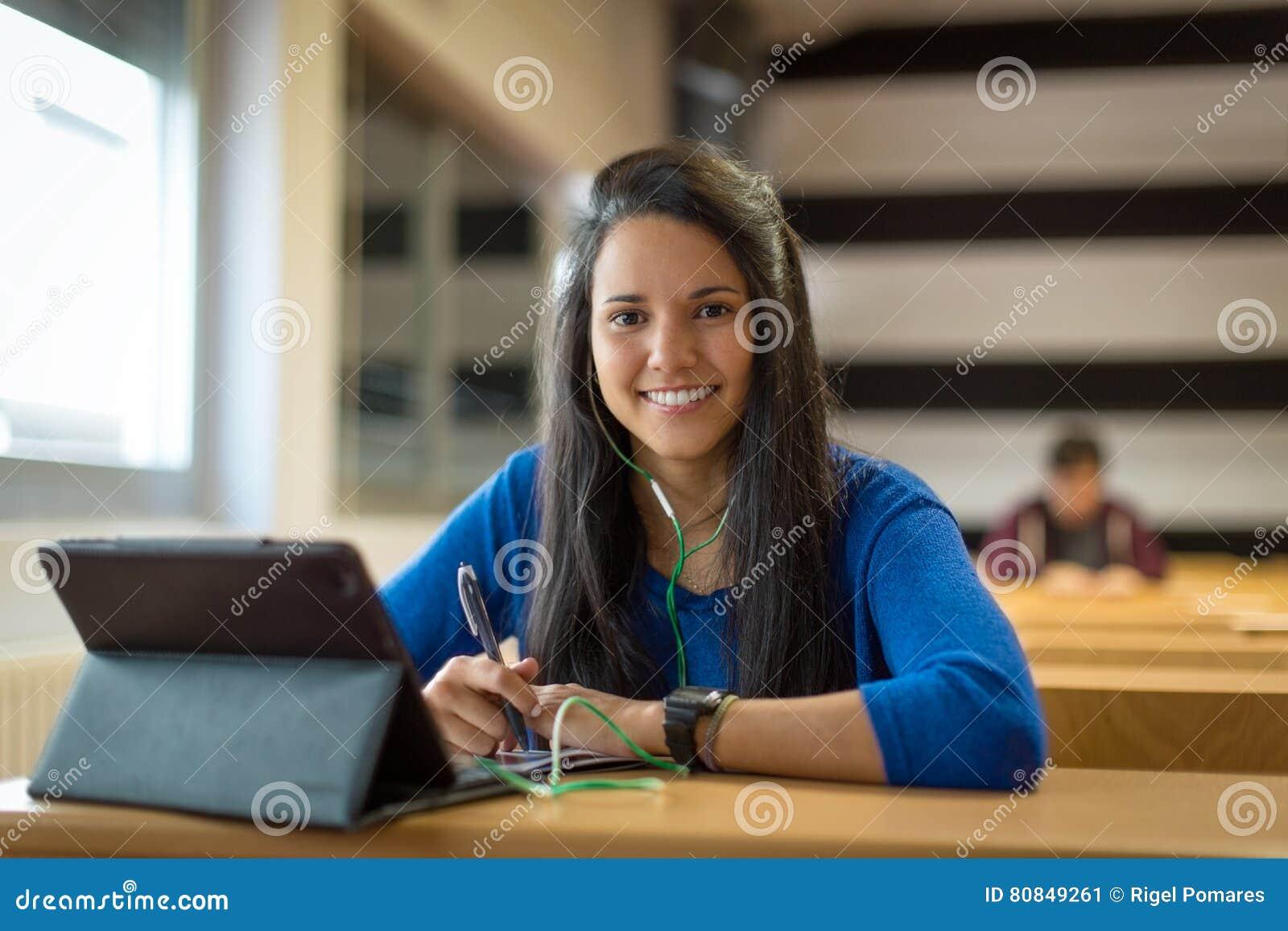Νέα γυναίκα σπουδαστής στην πανεπιστημιακή τάξη Αυτή ` s χρησιμοποιώντας την ταμπλέτα και τα ακουστικά για τη λήψη των σημειώσεων