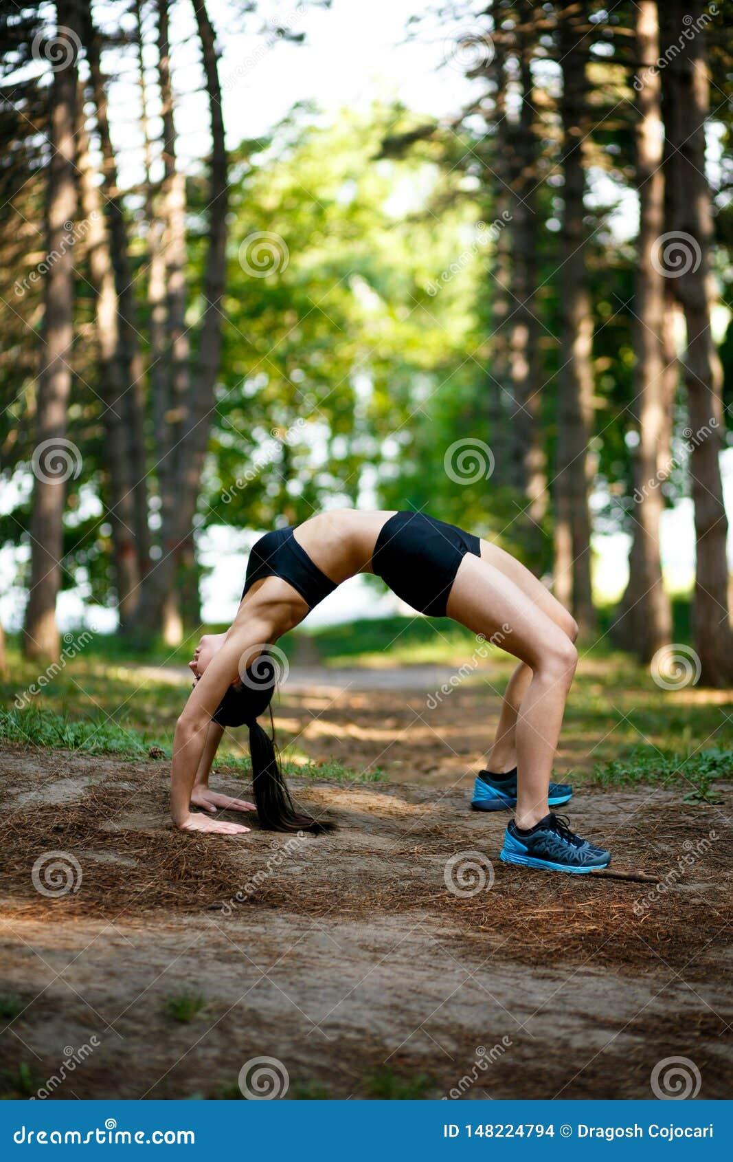 Νέα γυναίκα στη sportwear να κάνει δύναμη που ασκείται στο θερινό πάρκο Αθλητική άσκηση υπαίθρια