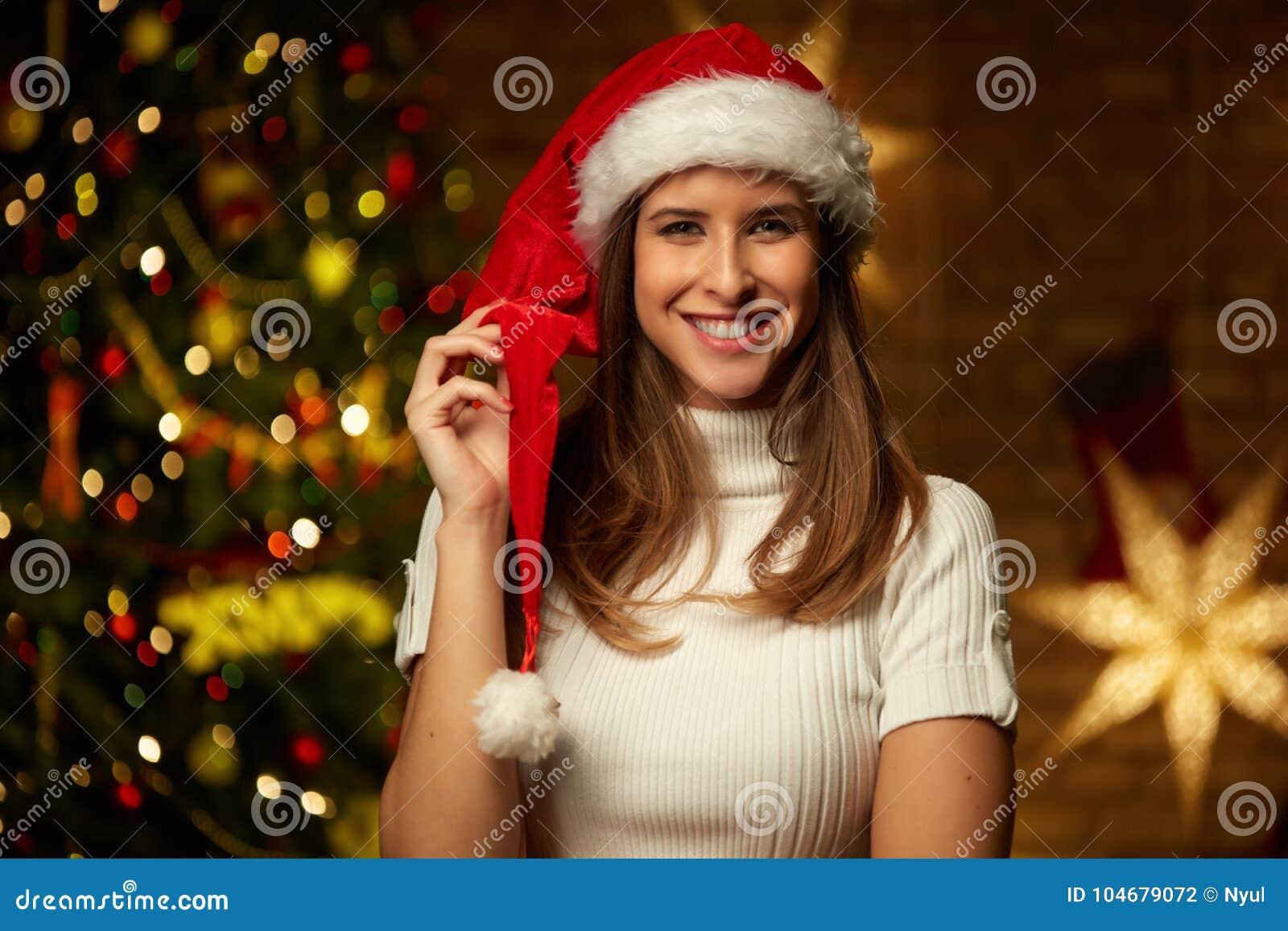 Νέα γυναίκα στο καπέλο santa με τα φω τα Χριστουγέννων