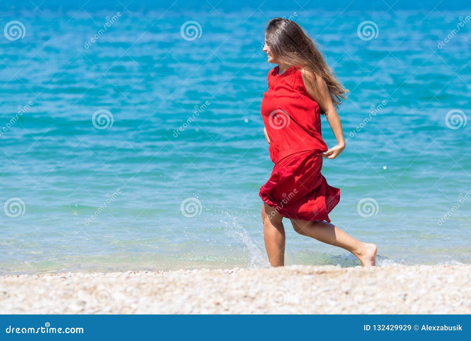 Νέα γυναίκα στο πολύ κόκκινο φόρεμα που τρέχει κατά μήκος της ακτής