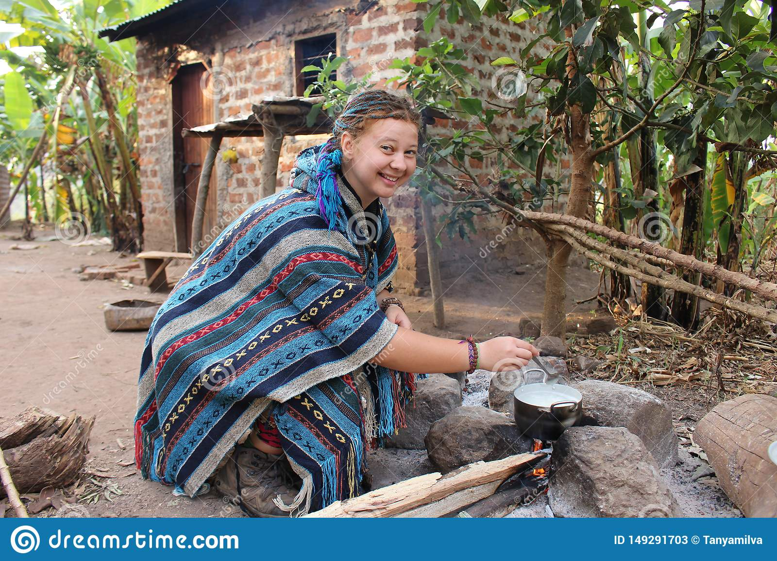 Νέα γυναίκα χίπηδων σε ένα μπλε poncho μαγείρεμα σε μια πυρά προσκόπων campground σε ένα χωριό
