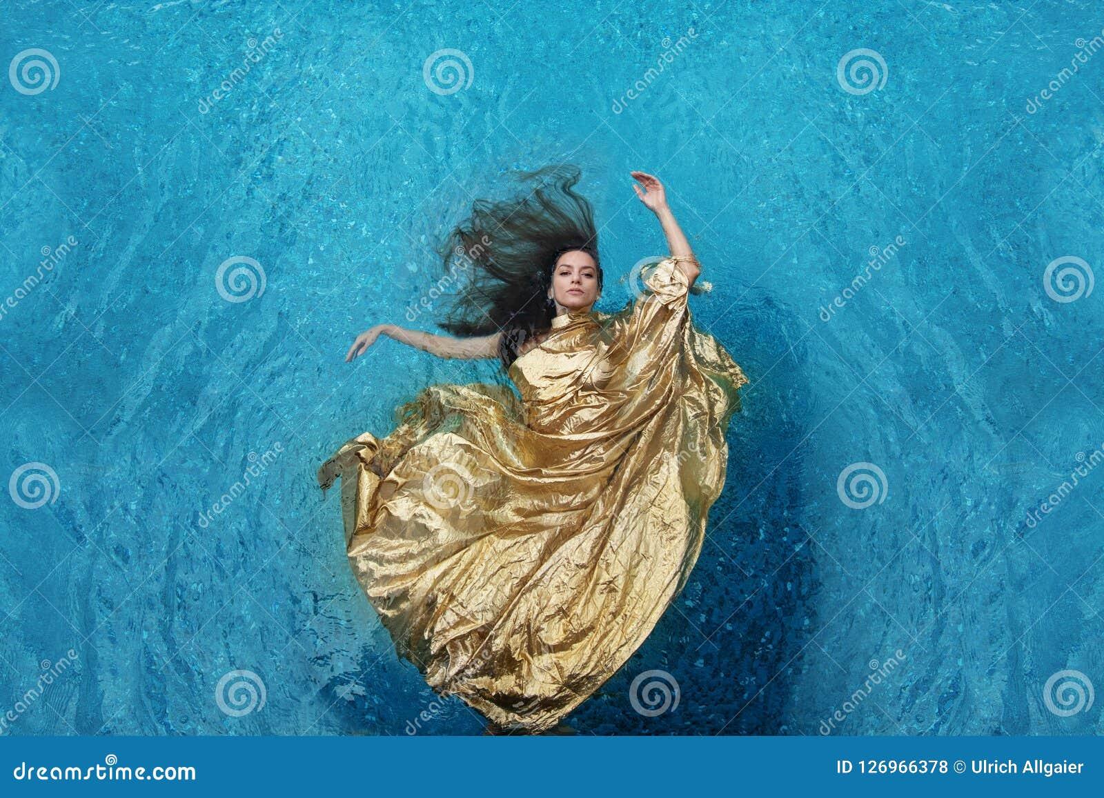 Νέα γυναίκα Bbeautiful στο χρυσό φόρεμα, που εξισώνει το φόρεμα που επιπλέει weightlessly κομψό να επιπλεύσει στο νερό στη λίμνη