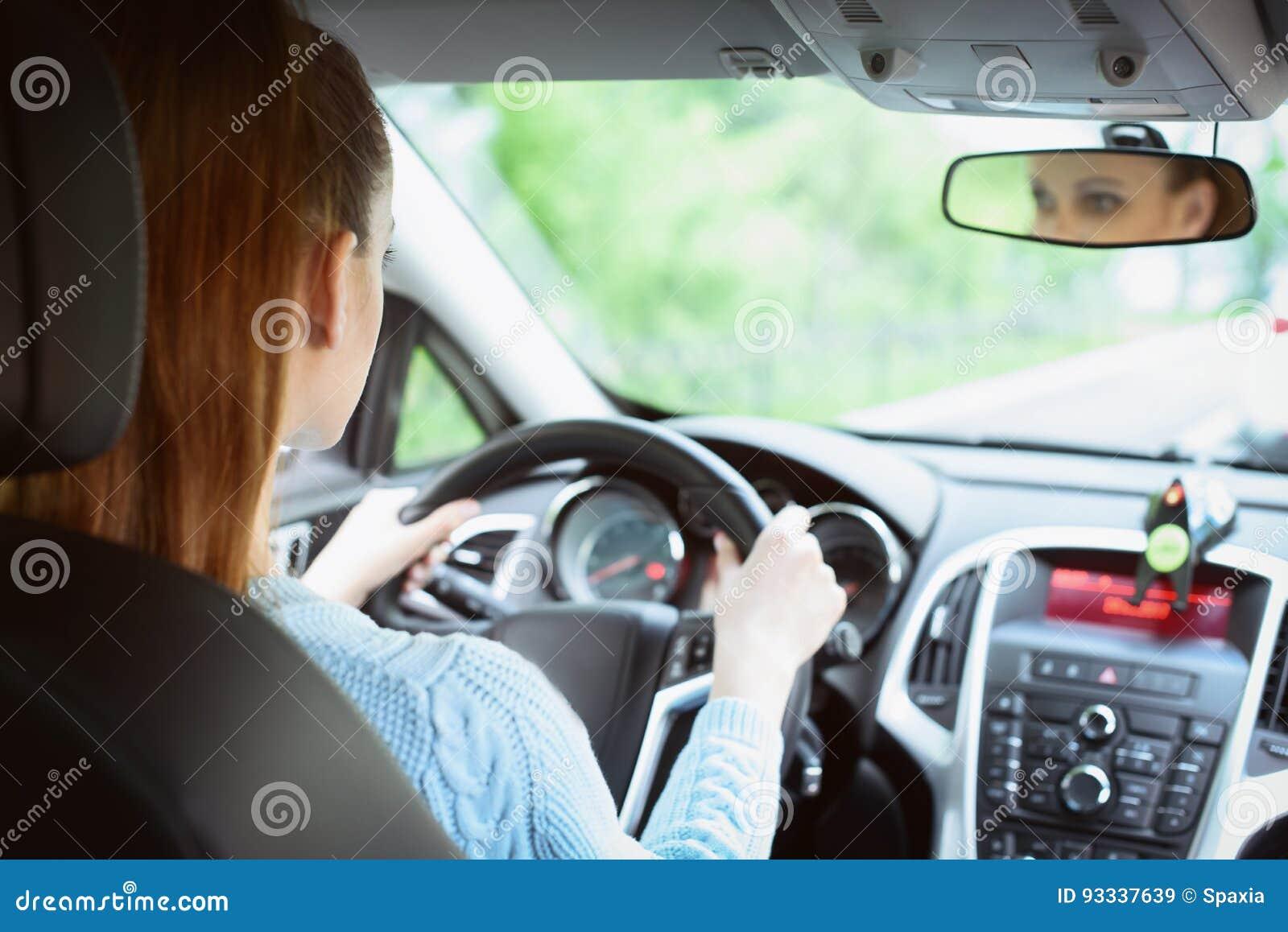 Νέα γυναίκα brunette που οδηγεί ένα αυτοκίνητο