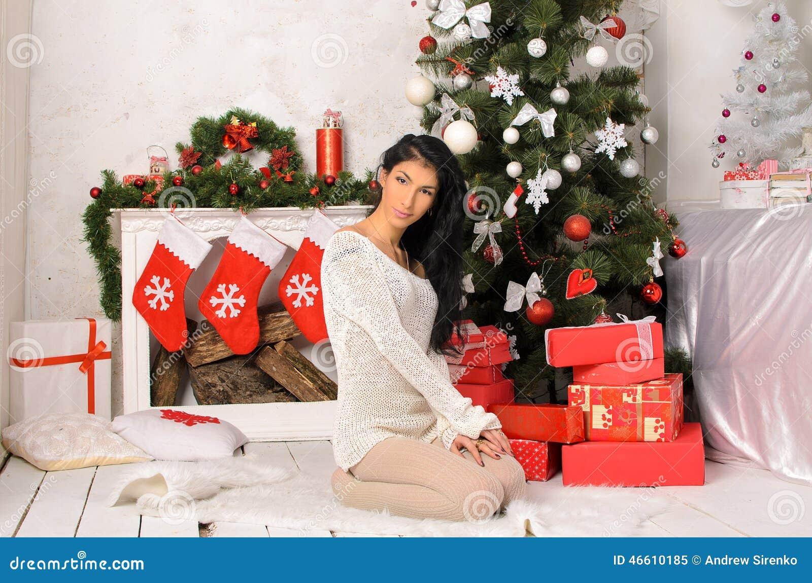 Νέα γυναίκα brunette στο εσωτερικό Χριστουγέννων