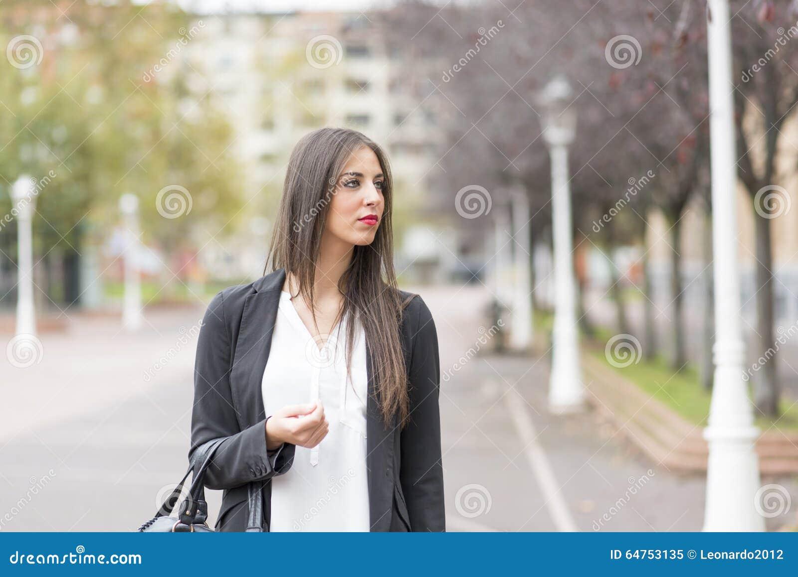 Νέα γυναίκα Elegand στην οδό που κοιτάζει μακριά