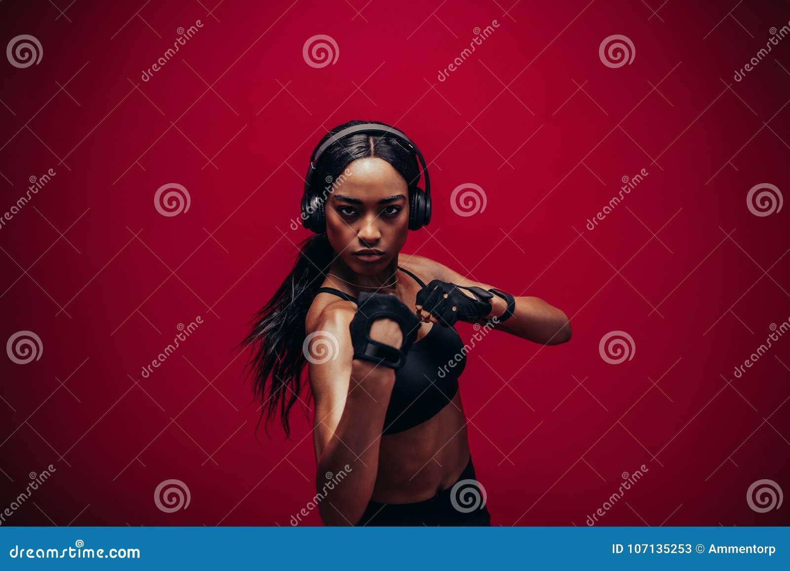Νέα γυναίκα sportswear στον εγκιβωτισμό στο κόκκινο υπόβαθρο