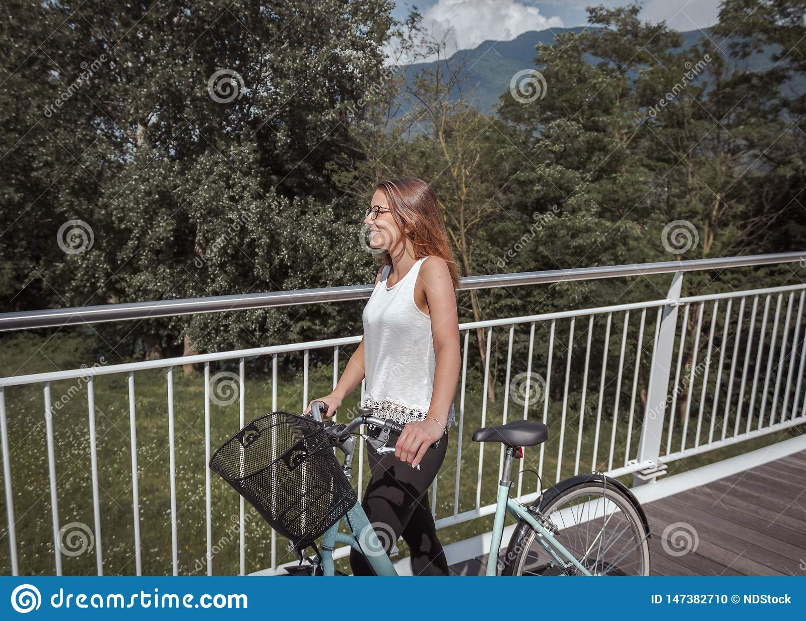 Νέα ελκυστική γυναίκα με το ποδήλατο σε μια γέφυρα