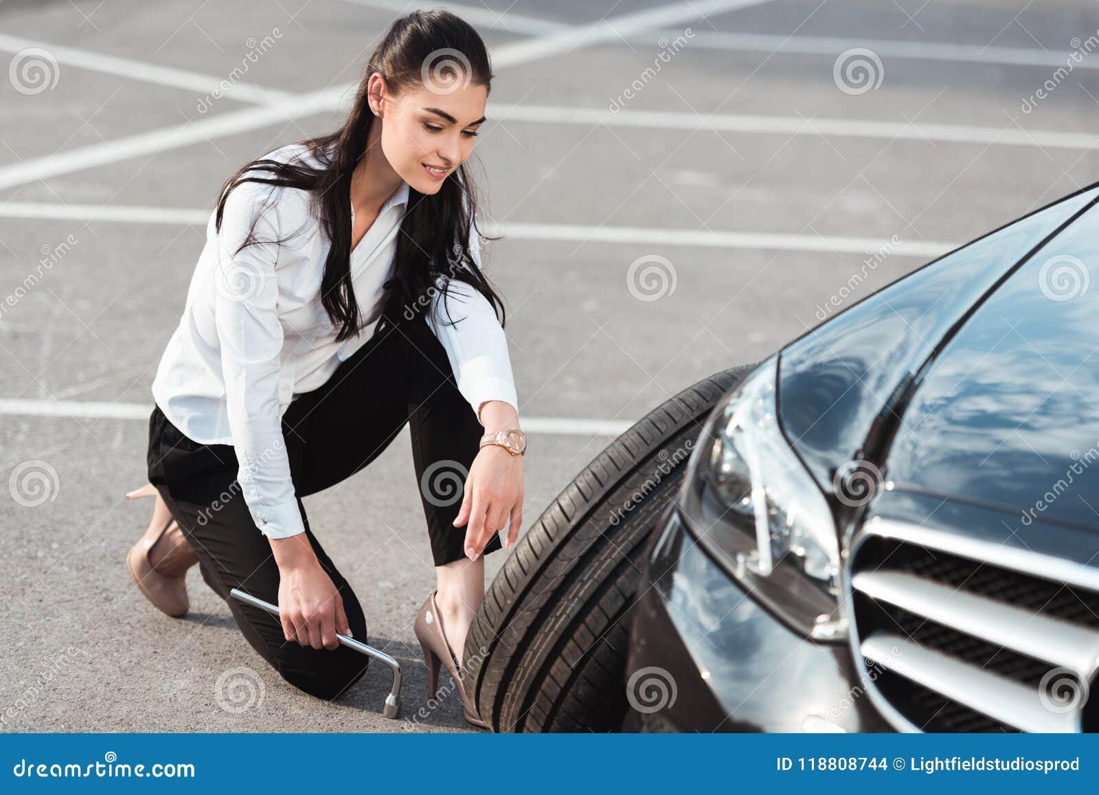 Νέα ελκυστική γυναίκα στην επίσημη ένδυση που κάθεται οκλαδόν κοντά στη ρόδα αυτοκινήτων με lug το γαλλικό κλειδί