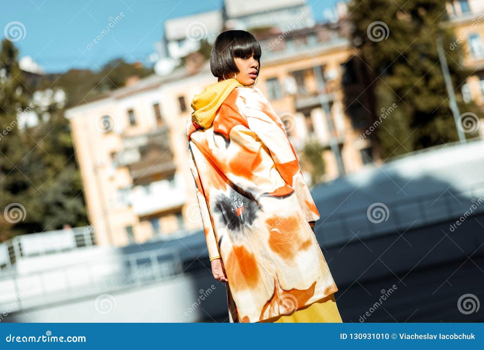 Νέα ελκυστική κυρία που φορά τυπωμένο το λουλούδι επενδύτη