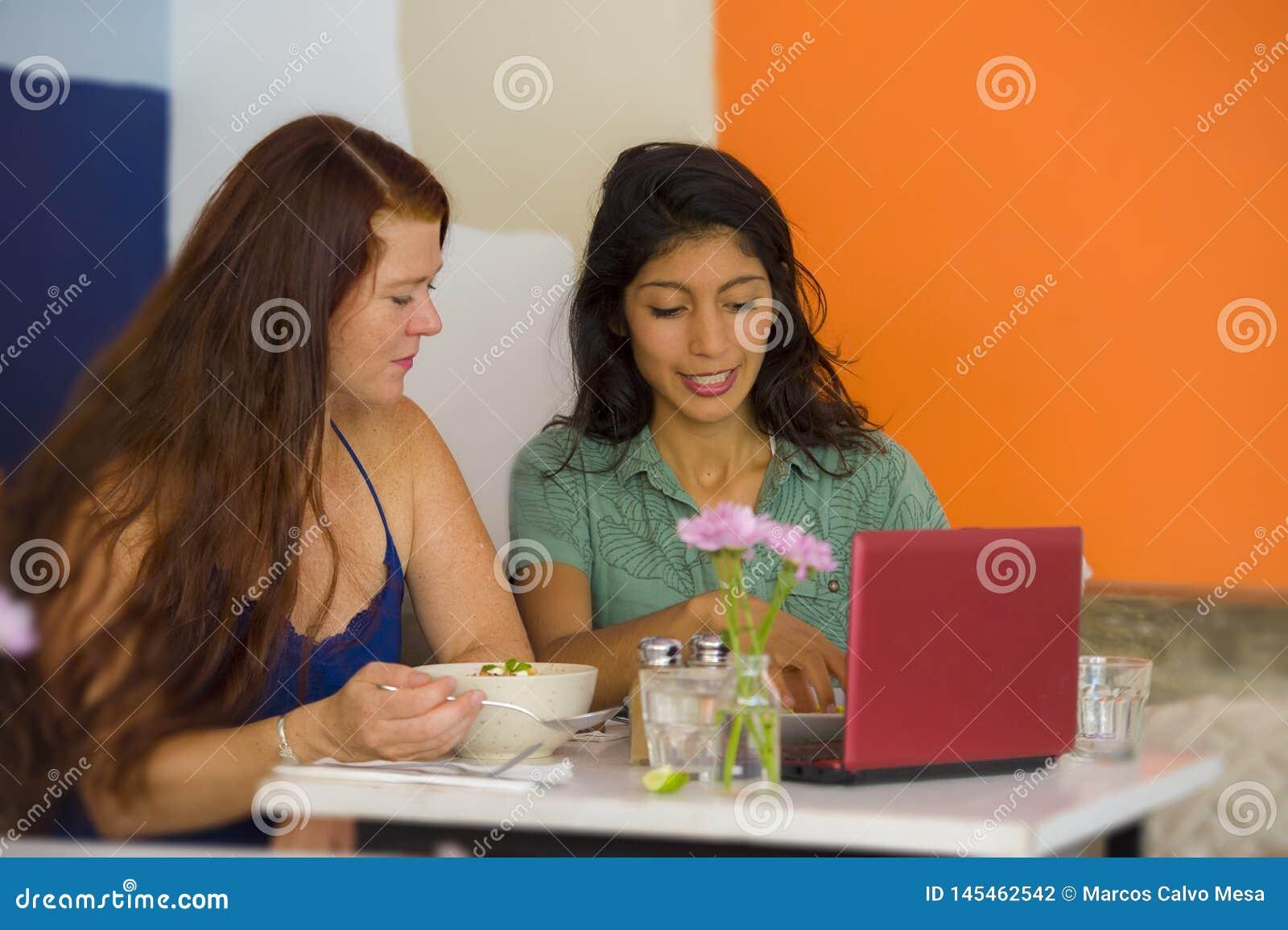 Νέα ελκυστική λατινική συνεδρίαση κοριτσιών στο σύγχρονο καφέ που έχει το μεσημεριανό γεύμα με την ευτυχή γυναίκα ως φίλες που συ