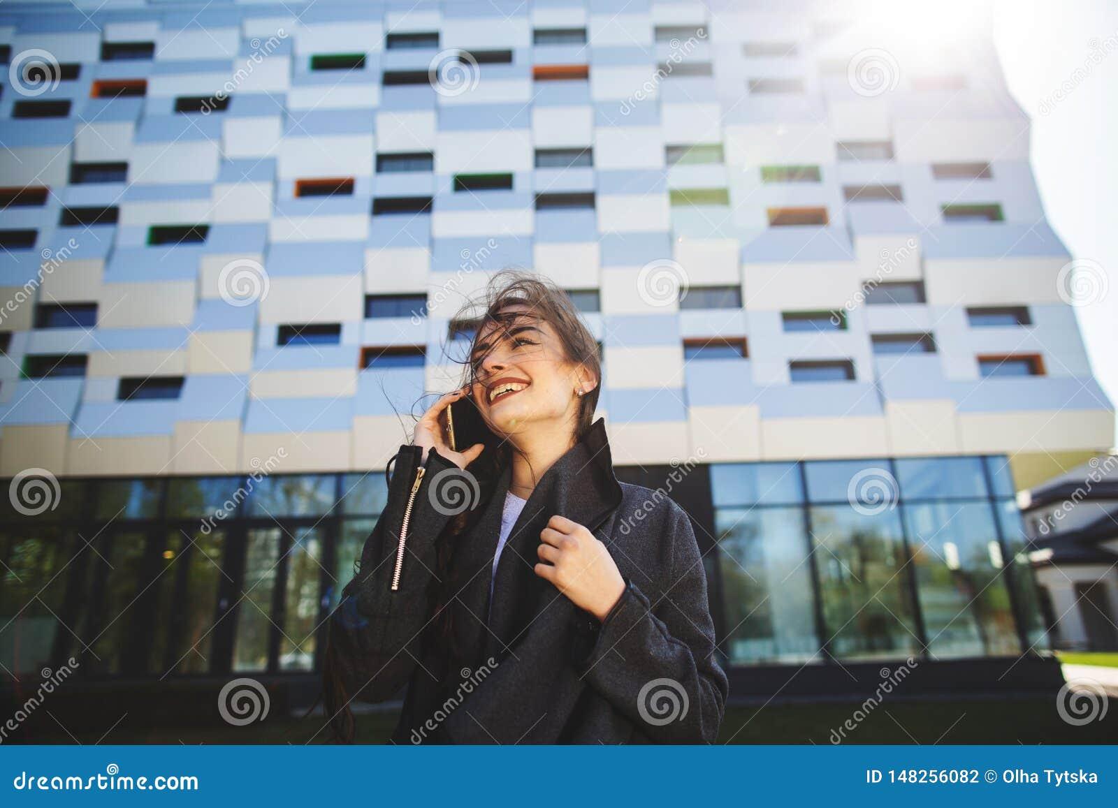 Νέα επιχειρηματίας που μιλά στο κινητό τηλέφωνο κατά τη διάρκεια του υπαίθριου διαλείμματος, κοντά στο κτίριο γραφείων Έννοια επι