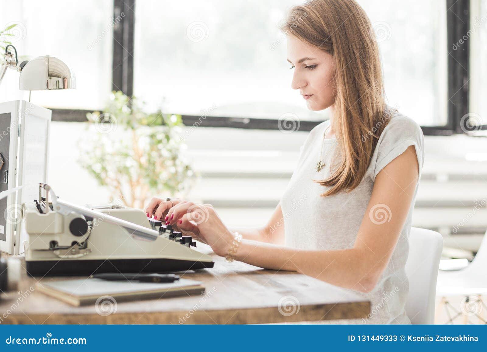 Νέα επιχειρησιακή γυναίκα που εργάζεται στο σπίτι και που δακτυλογραφεί σε μια γραφομηχανή Δημιουργικός Σκανδιναβικός χώρος εργασ
