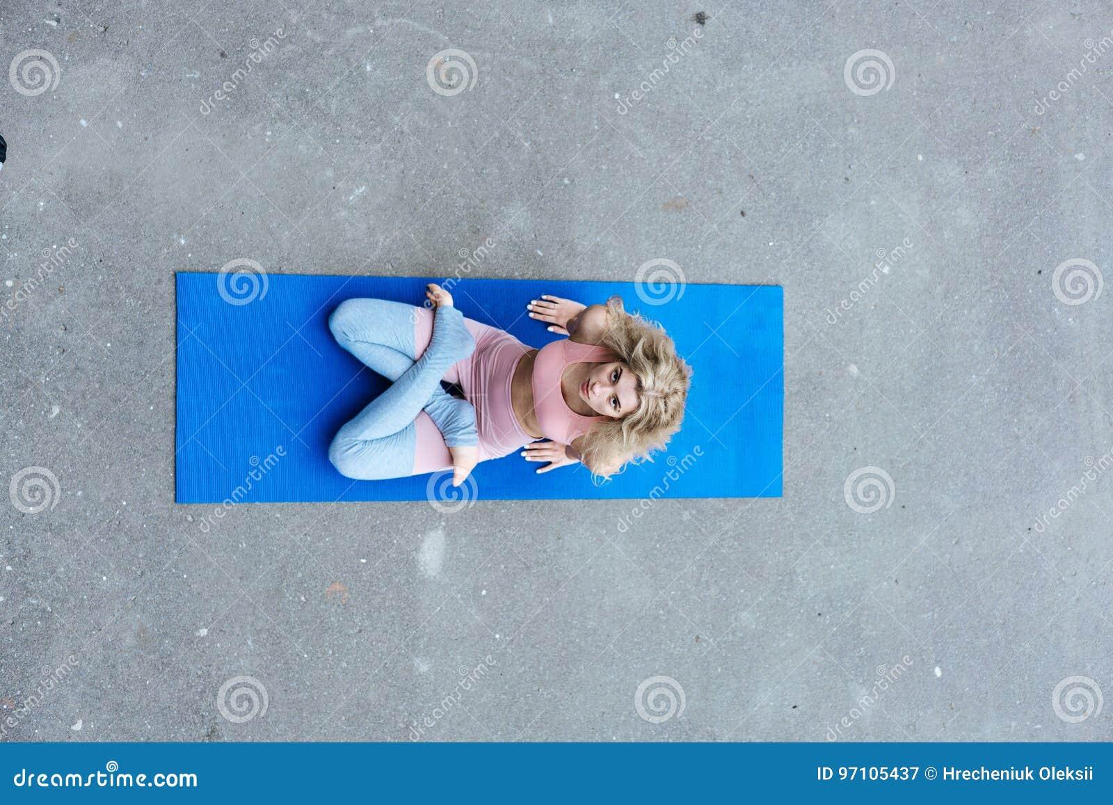 Νέα λεπτή ξανθή γυναίκα που κάνει τις ασκήσεις γιόγκας