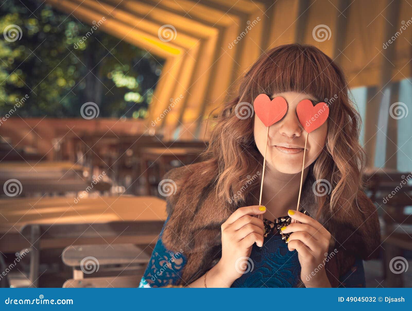 Νέα ευτυχής γυναίκα που κρατά δύο καρδιές