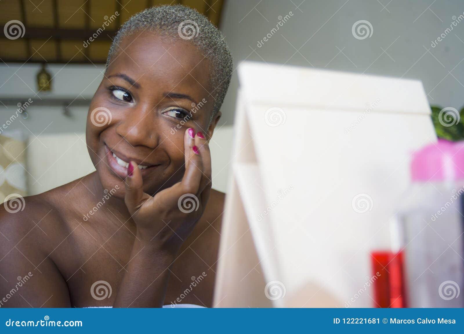 Νέα ευτυχής και ελκυστική αμερικανική γυναίκα μαύρων Αφρικανών που τυλίγεται στην πετσέτα που εφαρμόζει makeup τα καλλυντικά που