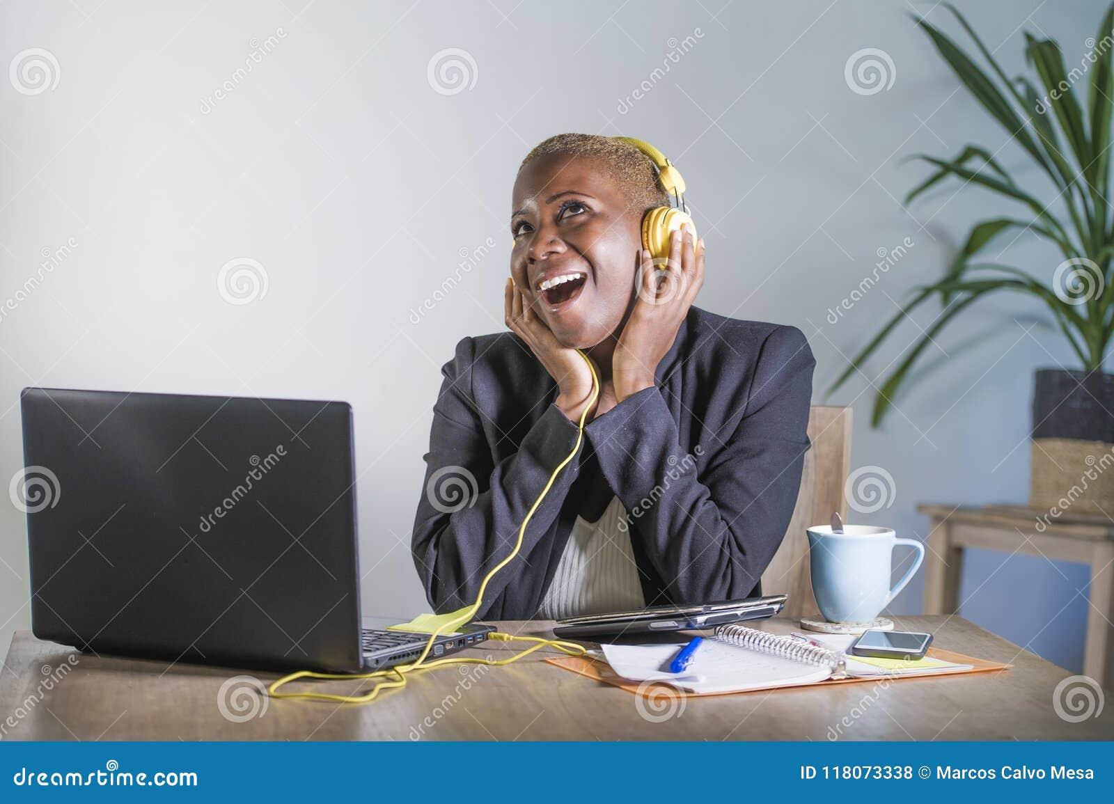 Νέα ευτυχής μαύρη αμερικανική γυναίκα afro που ακούει τη μουσική με τα ακουστικά που διεγείρονται και τη χαρούμενη εργασία στο γρ