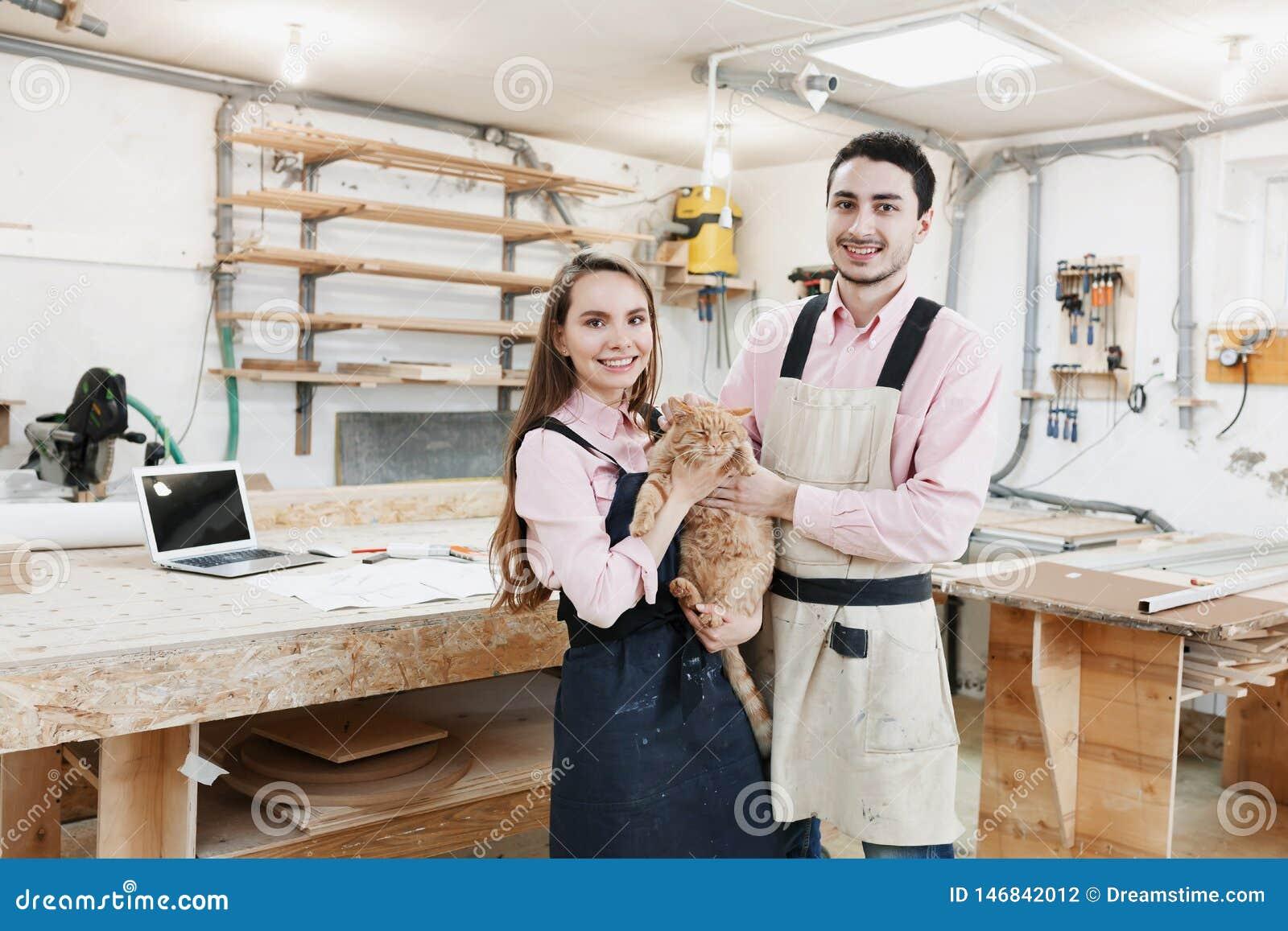 Νέα ευτυχής οικογένεια που εργάζεται στο εργαστήριο ξυλουργών
