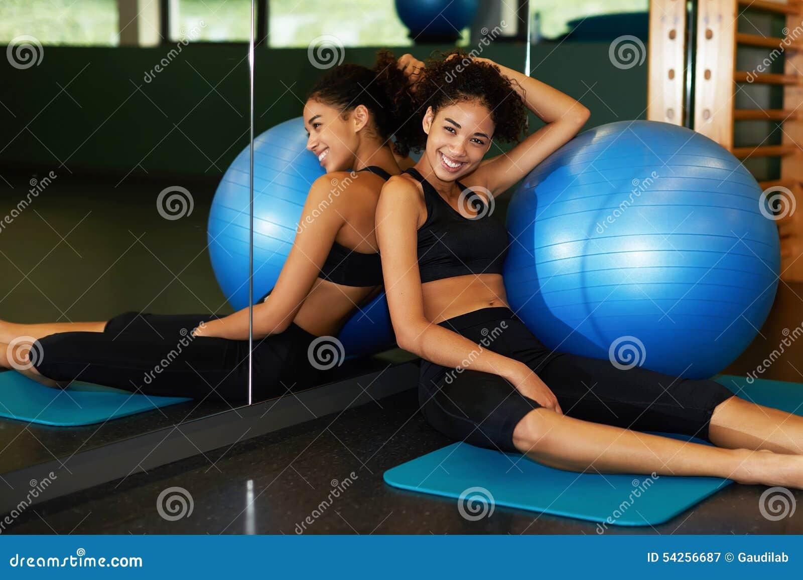 Νέα ευτυχής χαλάρωση γυναικών μετά από τη συνεδρίαση κατηγορίας Pilates με την κατάλληλη σφαίρα στο χαλί