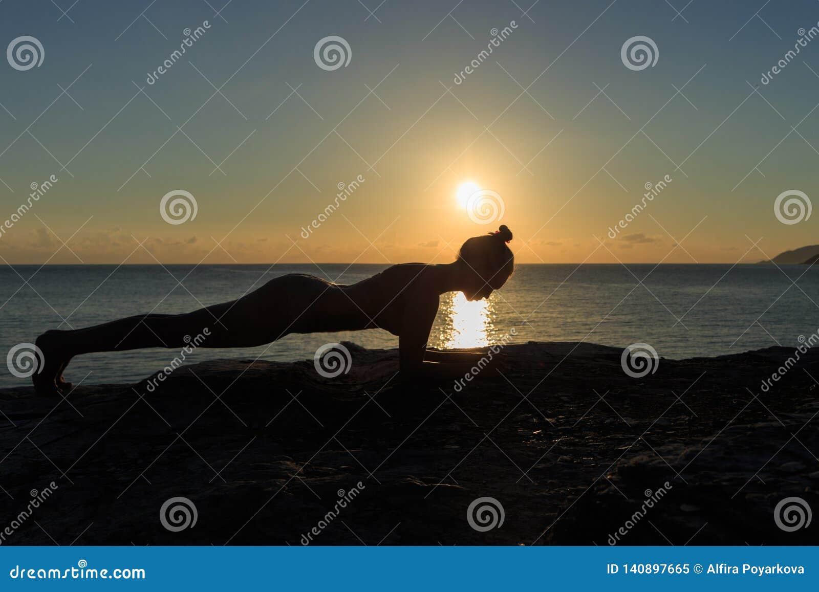 Νέα θηλυκή σκιαγραφία που κάνει την άσκηση σανίδων σε μια παραλία στην ανατολή
