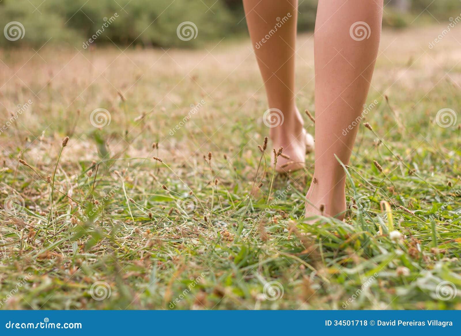 Νέα θηλυκά πόδια που περπατούν στη χλόη
