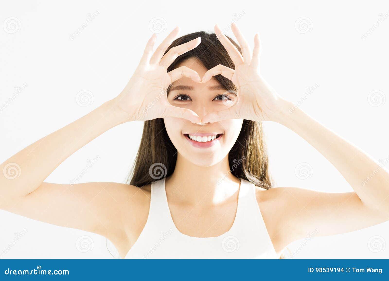 νέα διαμορφωμένα καρδιά χέρια εκμετάλλευσης γυναικών κοντά στα μάτια