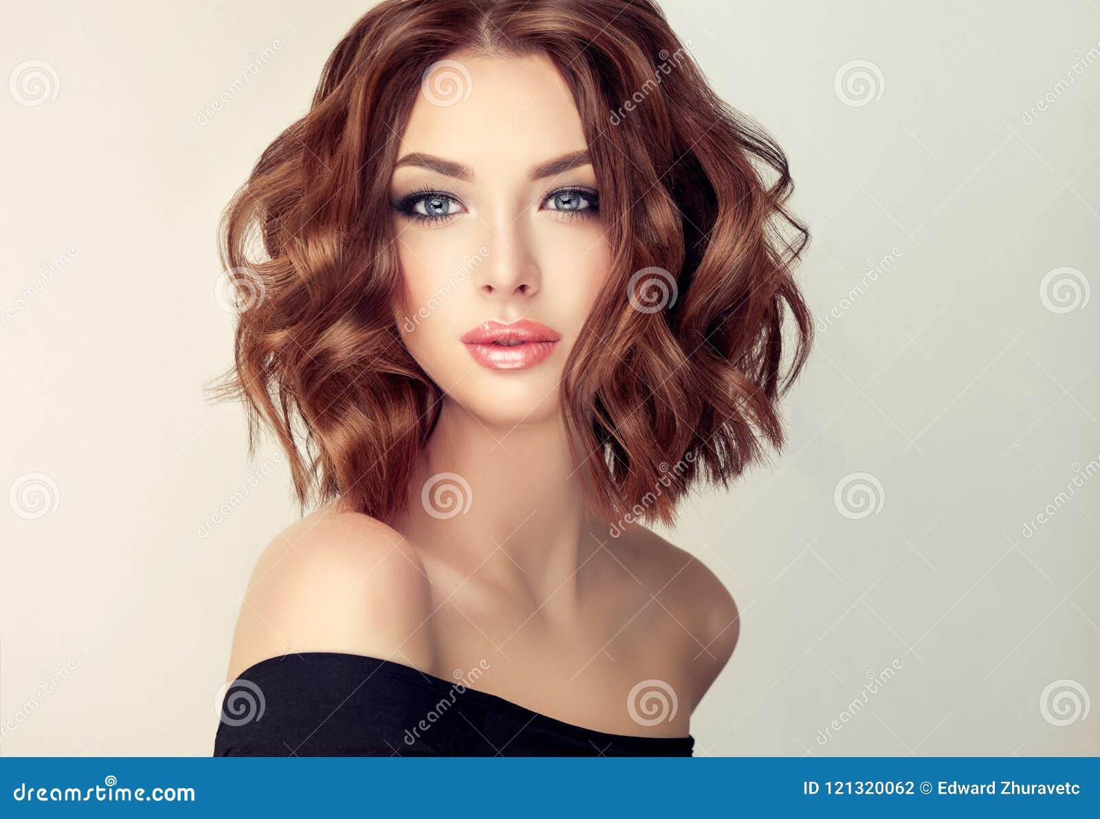 Νέα και ελκυστική καφετιά μαλλιαρή γυναίκα με το σύγχρονο, καθιερώνον τη μόδα και κομψό hairstyle