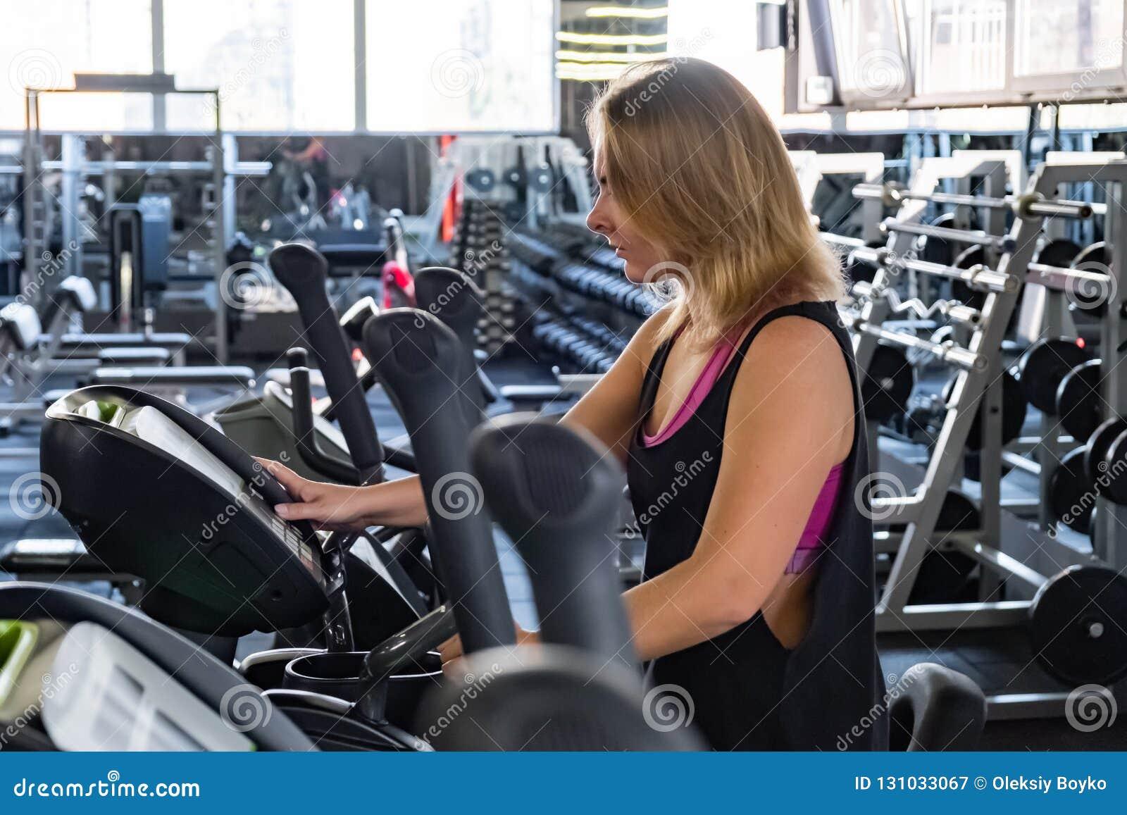 Νέα κατάλληλη γυναίκα στη γυμναστική που χρησιμοποιεί τον ελλειπτικό διαγώνιο εκπαιδευτή Femal