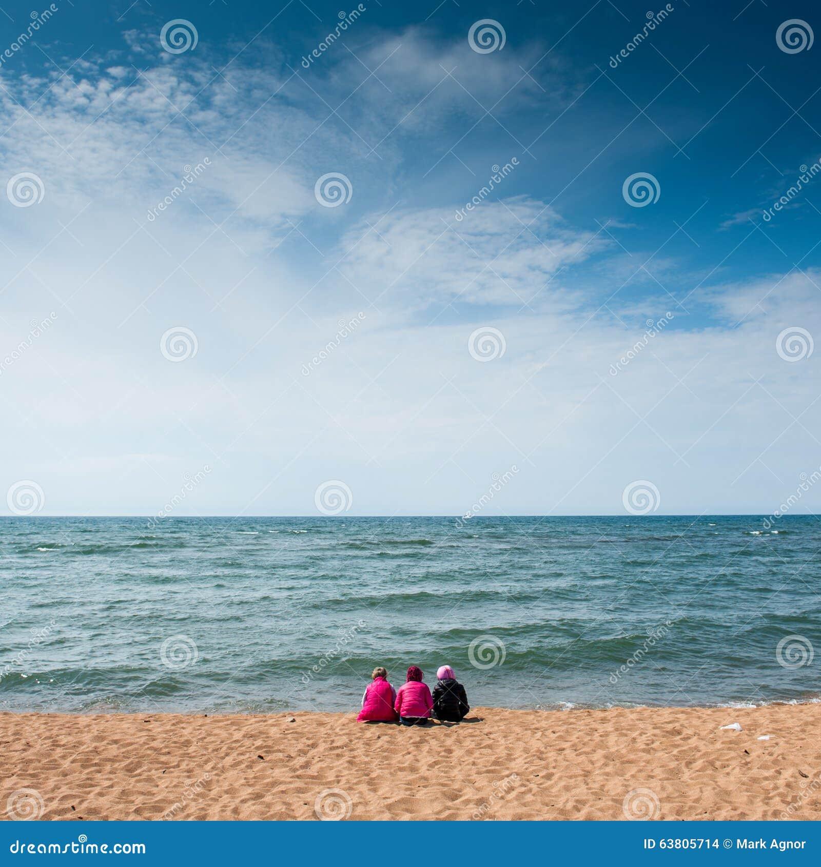Νέα κορίτσια που κάθονται στην ακτή της λίμνης Baikal το καλοκαίρι