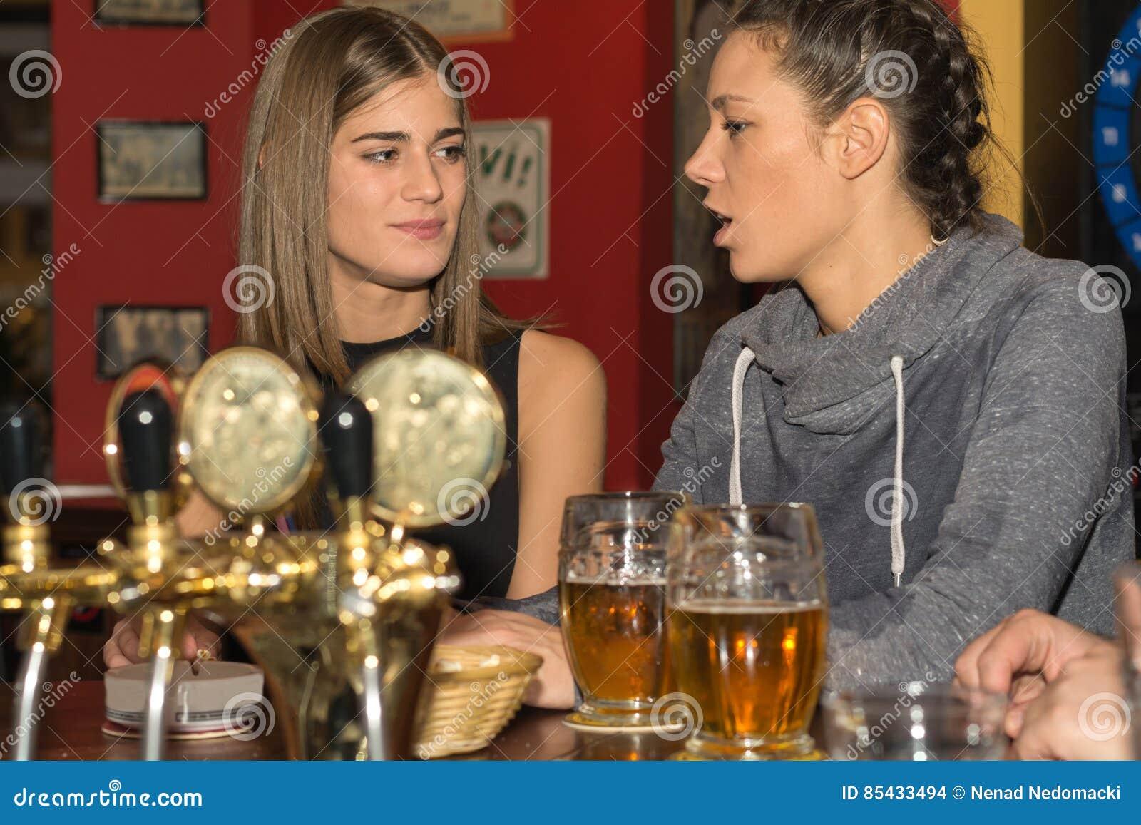 Νέα κορίτσια που πίνουν και που έχουν τη διασκέδαση από κοινού