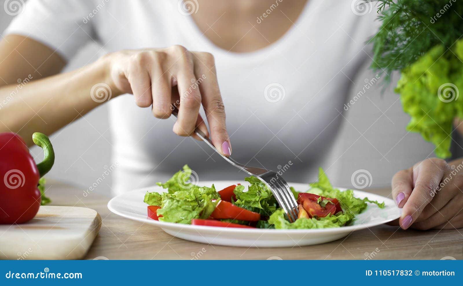 Νέα κυρία που παίρνει το δίκρανο σαλάτας ντοματών από το πιάτο γευμάτων, υγιές πρόχειρο φαγητό, βιταμίνες