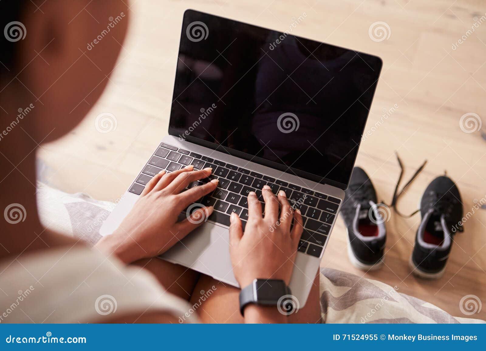 Νέα μαύρη γυναίκα που χρησιμοποιεί το φορητό προσωπικό υπολογιστή, άποψη πέρα-ώμων