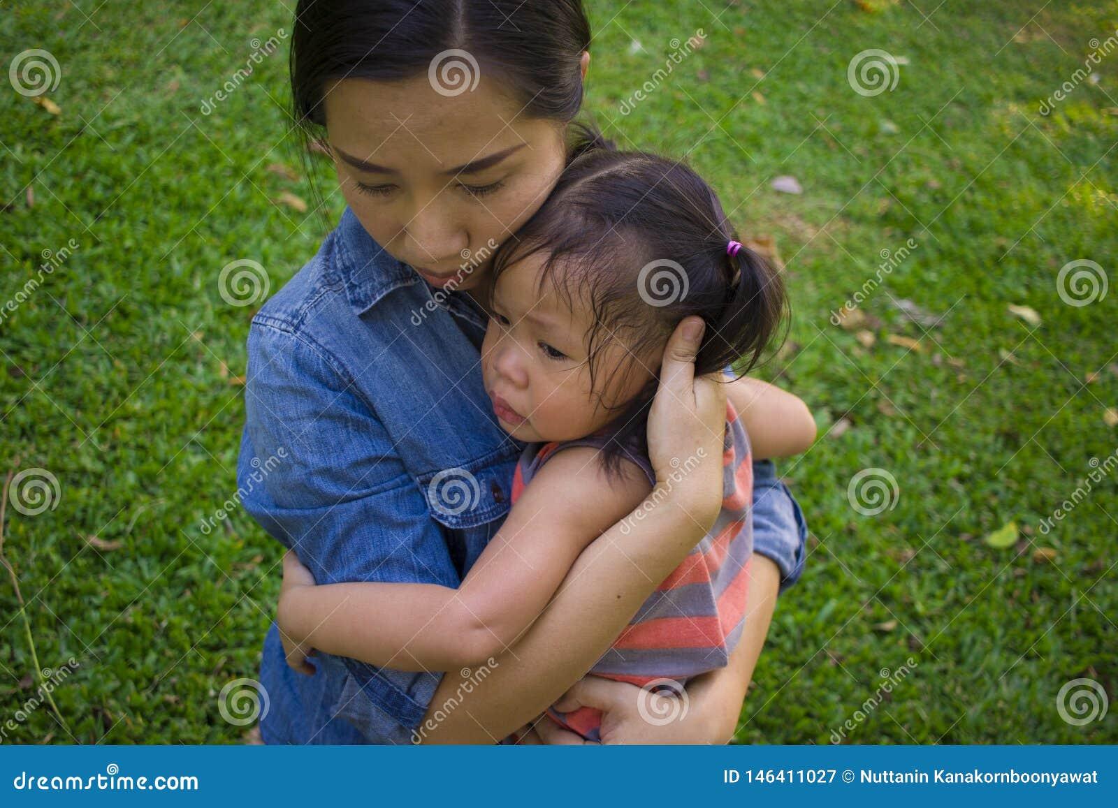 Νέα μητέρα που αγκαλιάζει και κατευναστική να φωνάξει λίγη κόρη, ασιατική μητέρα που προσπαθεί να ανακουφίσει και να ηρεμήσει κάτ