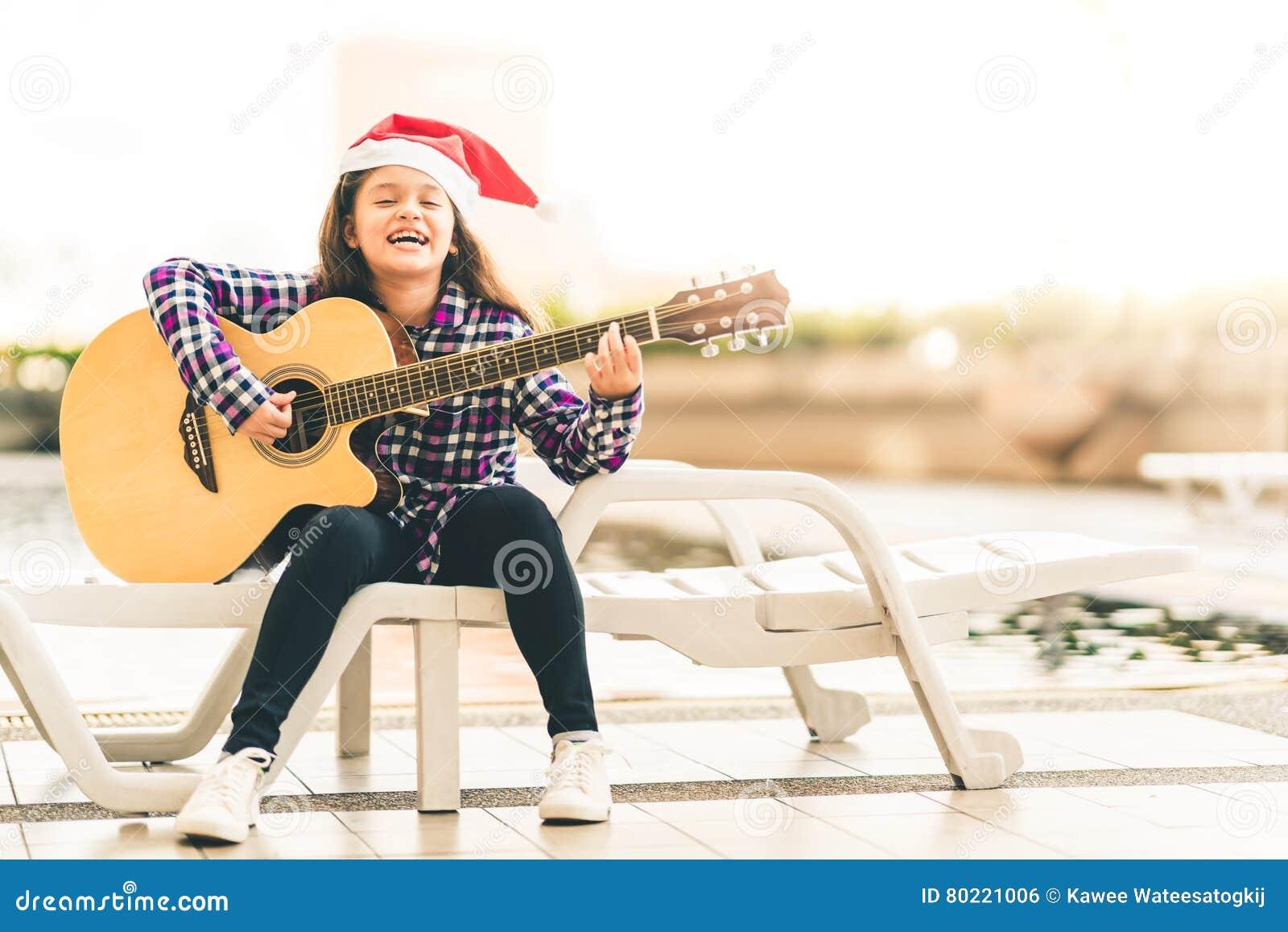Νέα μικτή κιθάρα παιχνιδιού κοριτσιών αγώνων, τραγούδι και χαμόγελο χαρωπά από την πισίνα, με το καπέλο santa Χριστουγέννων