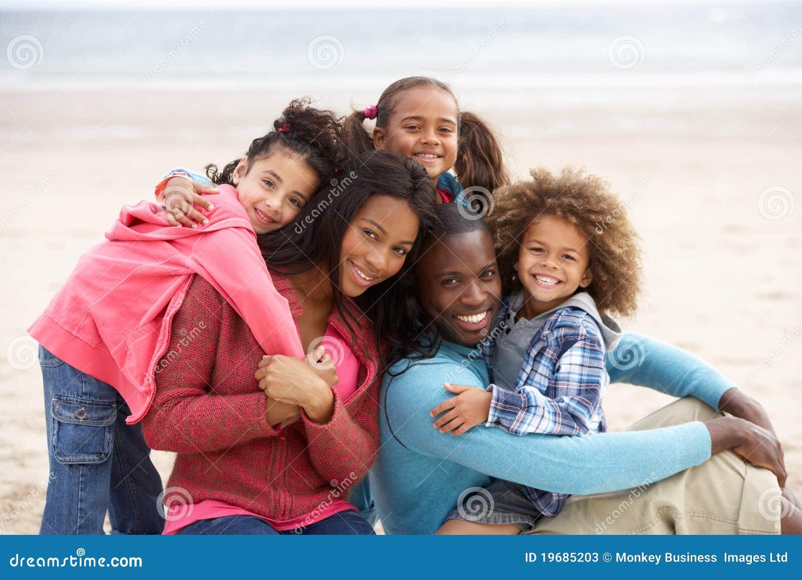 Νέα μικτή οικογένεια φυλών που αγκαλιάζει στην παραλία