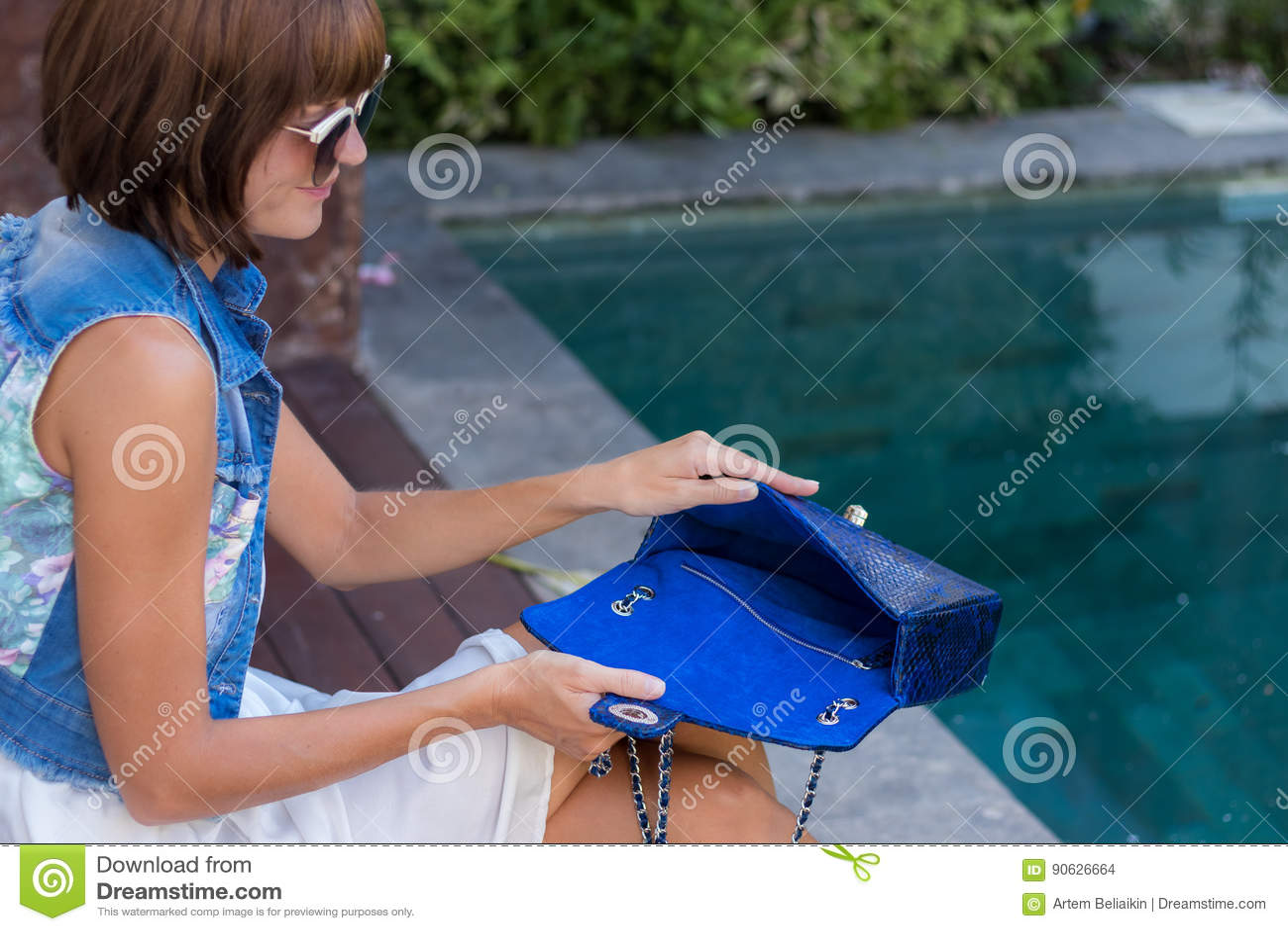 Νέα μοντέρνη γυναίκα στην καθιερώνουσα τη μόδα εξάρτηση με την τσάντα πολυτέλειας snakeskin python στα χέρια Γυναίκα με την τσάντ