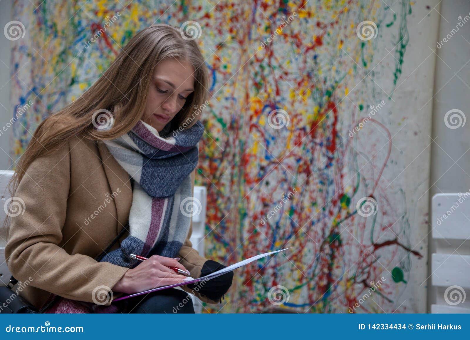 Νέα ξανθή γυναίκα που εγκαθιστά στον πάγκο και το γράψιμο