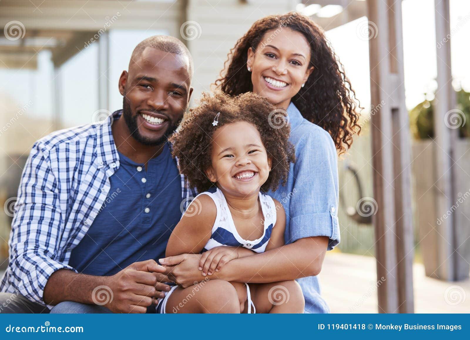 Νέα οικογένεια μαύρων που αγκαλιάζει υπαίθρια και που χαμογελά στη κάμερα