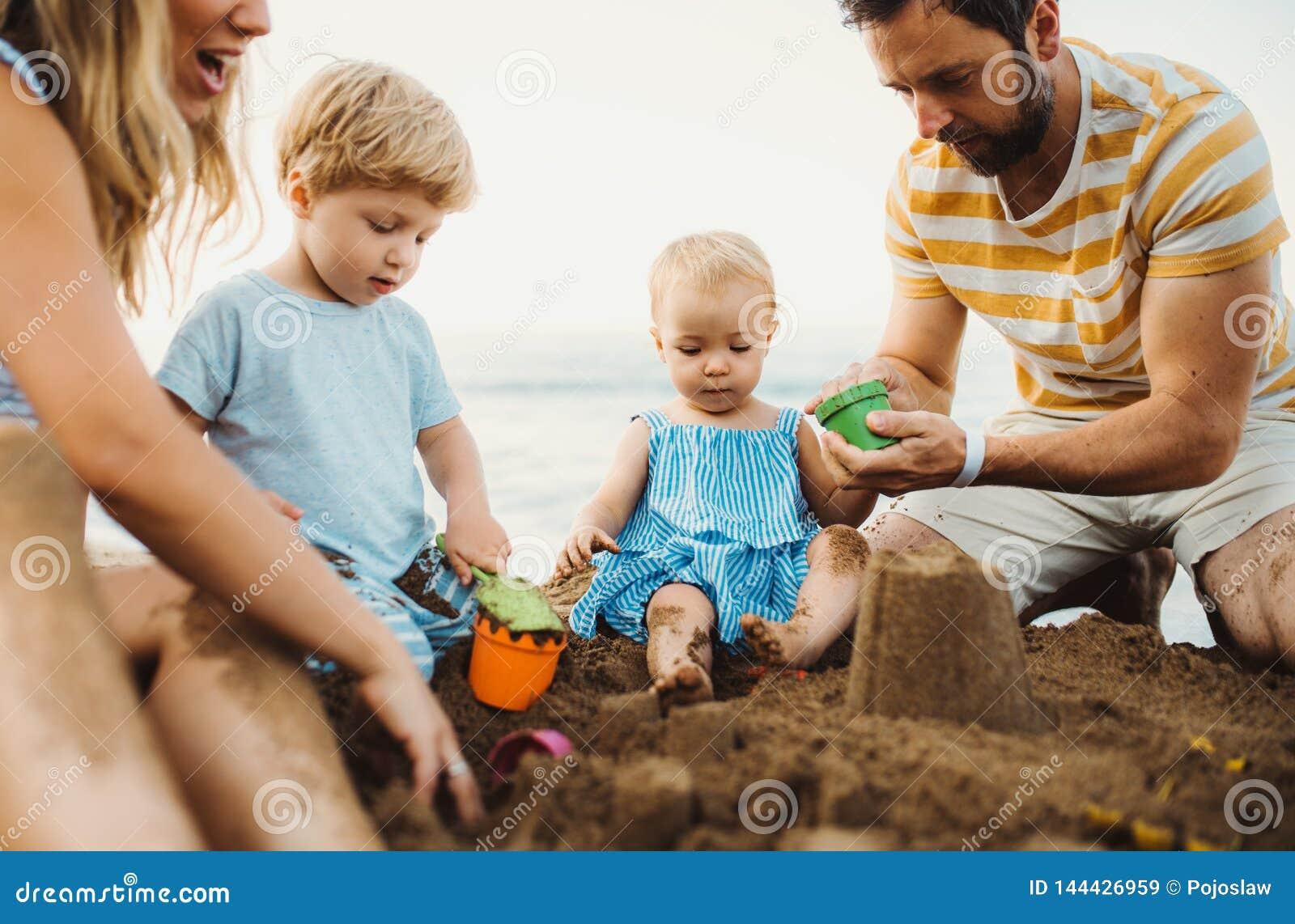 Νέα οικογένεια με τα παιδιά μικρών παιδιών που παίζουν με την άμμο στην παραλία στις καλοκαιρινές διακοπές