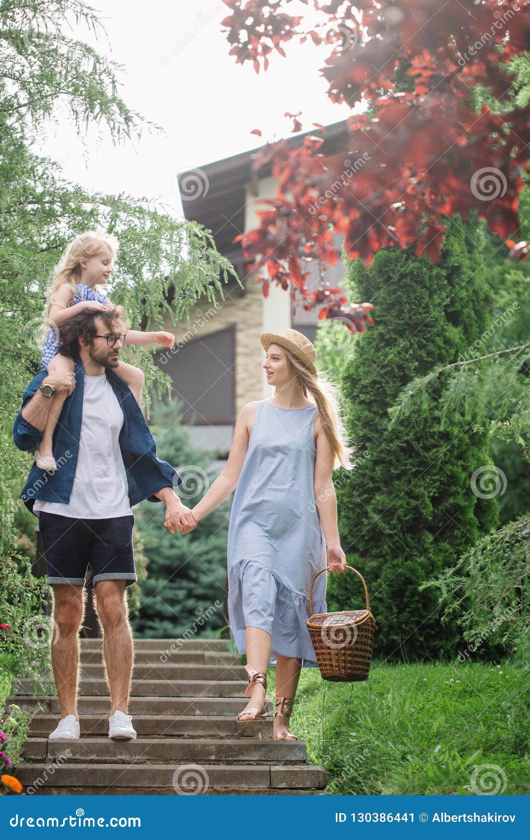 Νέα οικογένεια με το καλάθι μετά από το πικ-νίκ που περπατά κάτω από τα σκαλοπάτια έξω στο πράσινο πάρκο