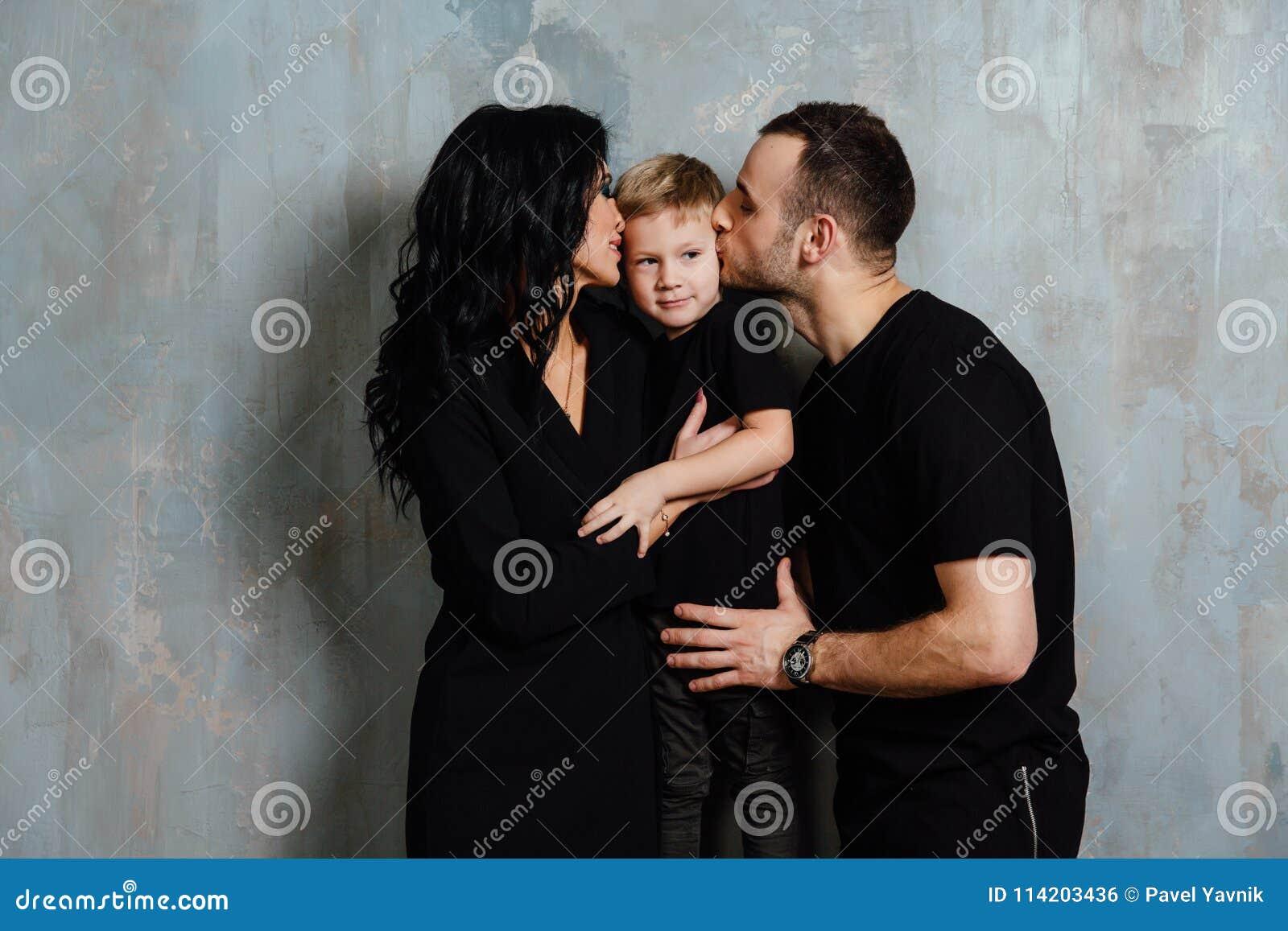 Νέα οικογένεια που έχει τη διασκέδαση στο σπίτι σε ένα υπόβαθρο ενός εκλεκτής ποιότητας κατασκευασμένου τοίχου