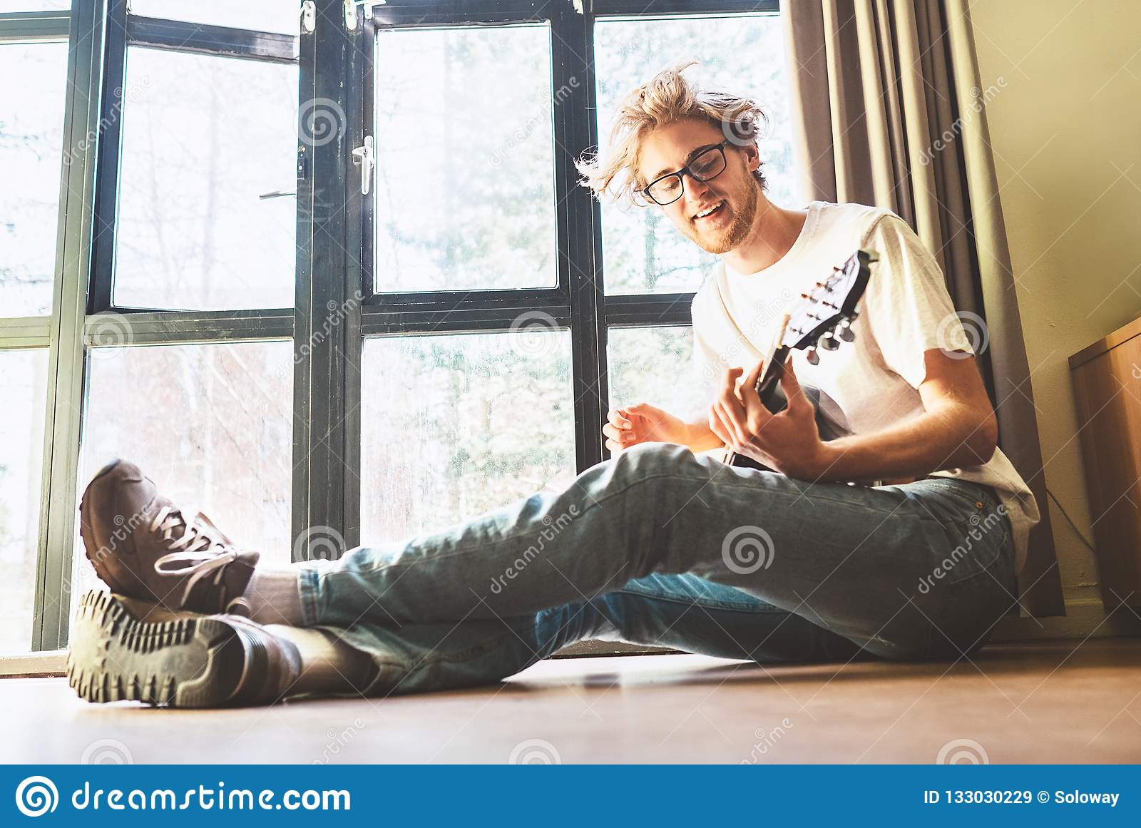 Νέα παιχνίδια ατόμων blondhair handsom στη συνεδρίαση κιθάρων στο nea πατωμάτων