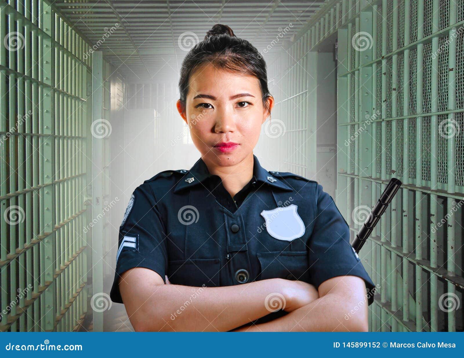 Νέα σοβαρή και ελκυστική ασιατική κορεατική γυναίκα φρουράς που στέκεται στο κύτταρο στο κρατικό σωφρονιστήριο που φορά την αστυν